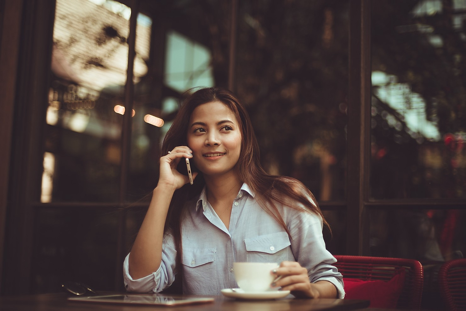 Young woman at a cafe speaking on the phone