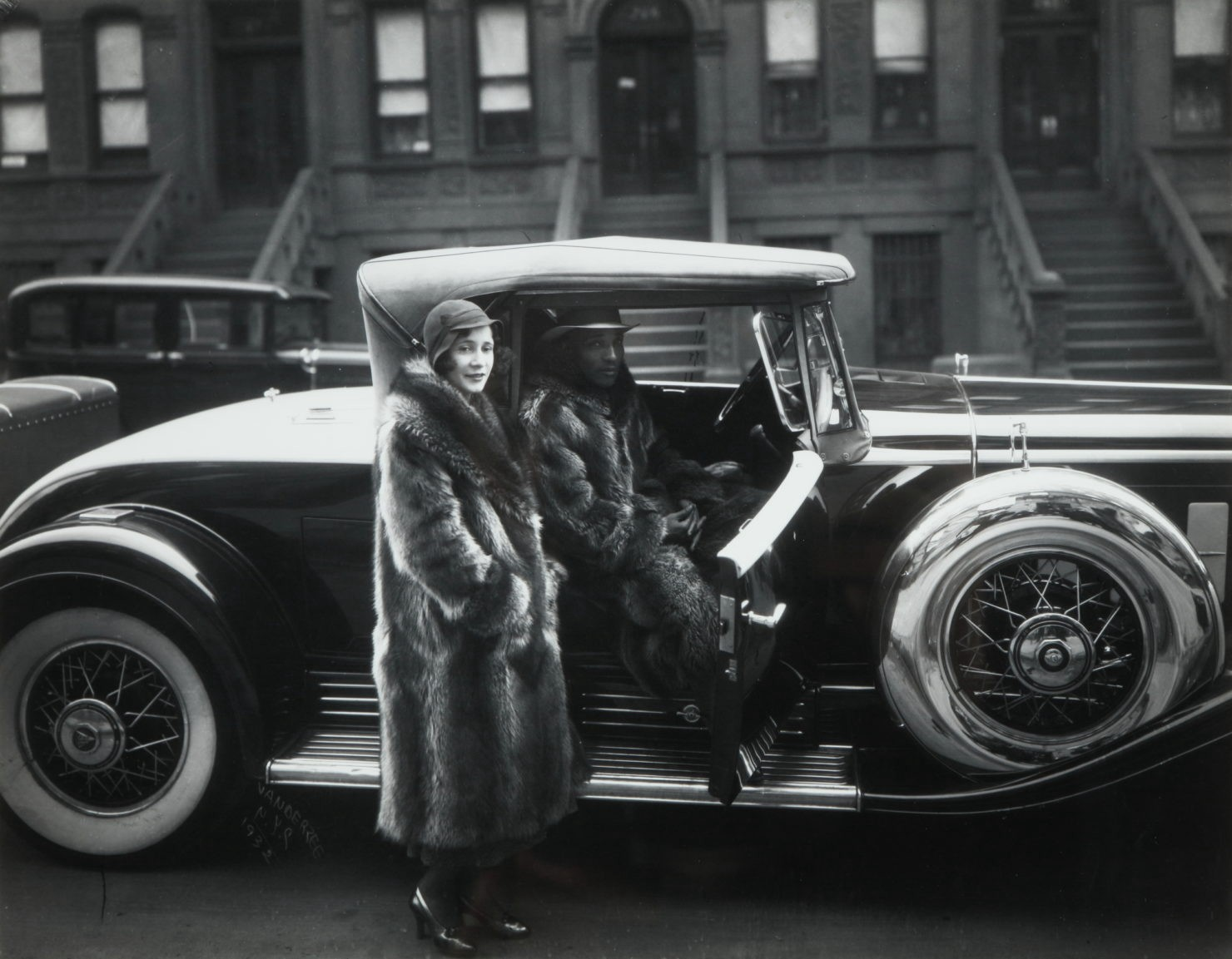 Black and white photograph of a black couple in 1920s Harlem wearing long fur coats as they enter their stylish automobile.