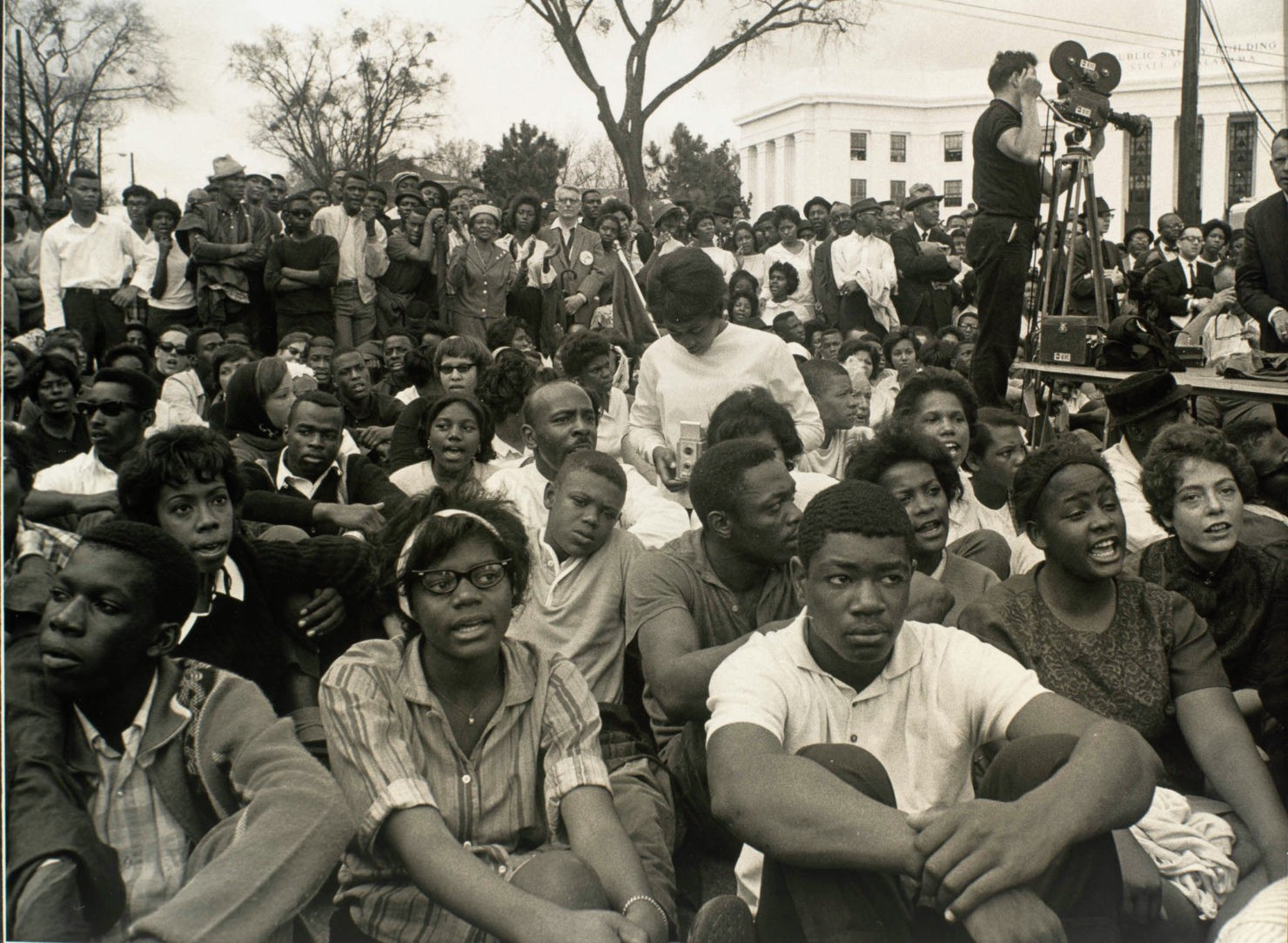 A crowd of black students sit together as photographers record the moment at the end of the march to Montgomery.