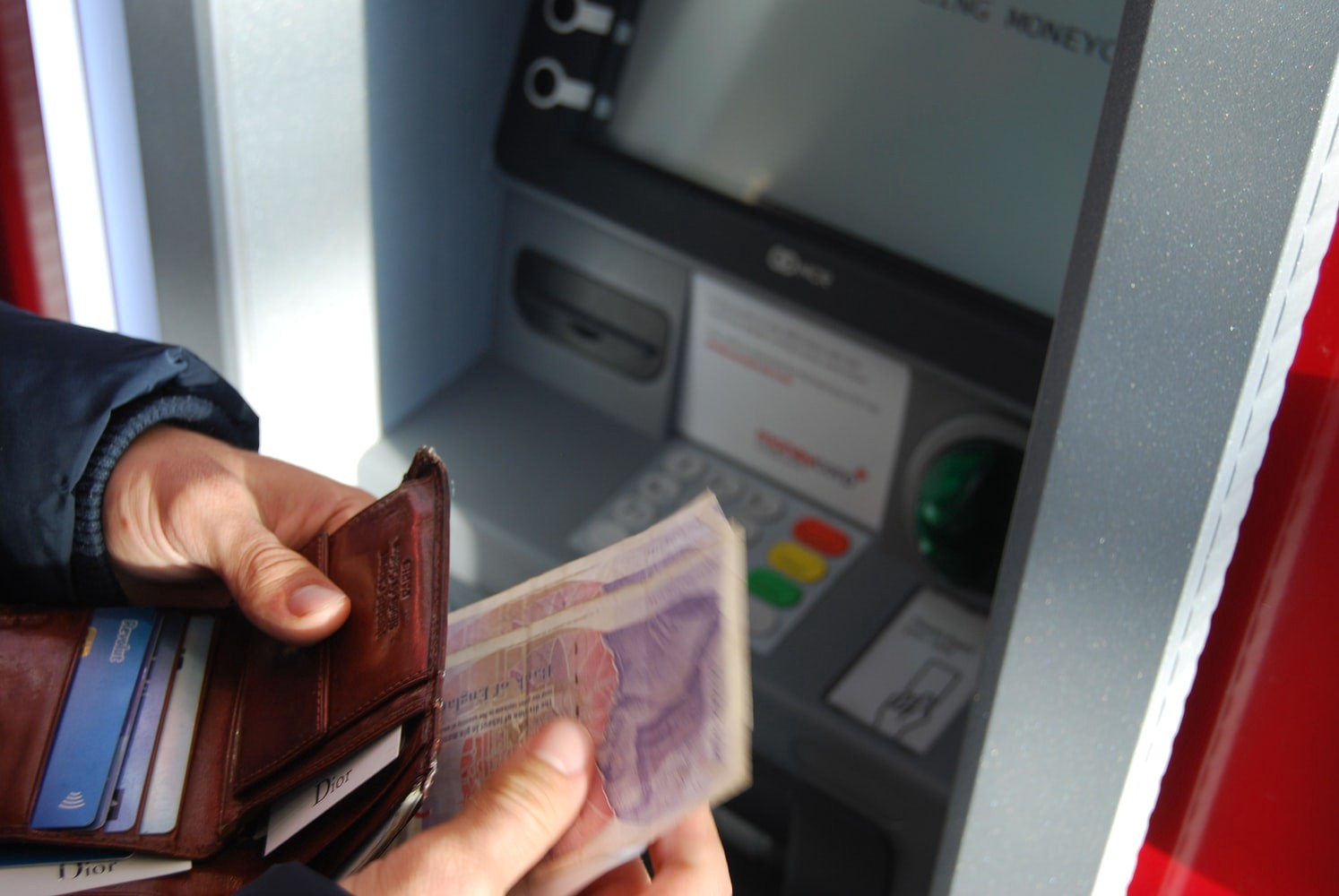 Holding money at an automated teller machine.