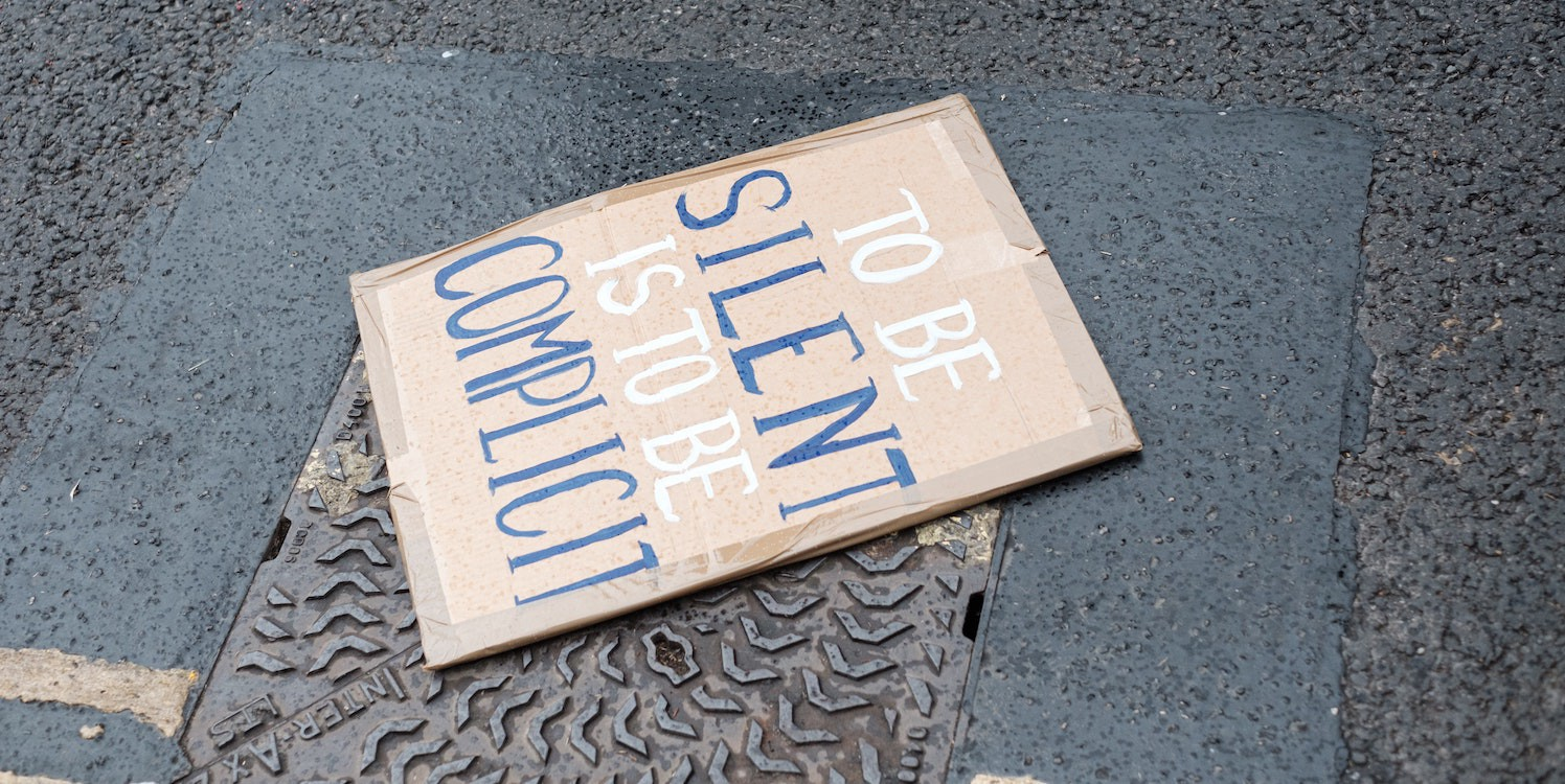"""Image of a protest sign on the ground saying """"to be silent is to be complicit"""""""