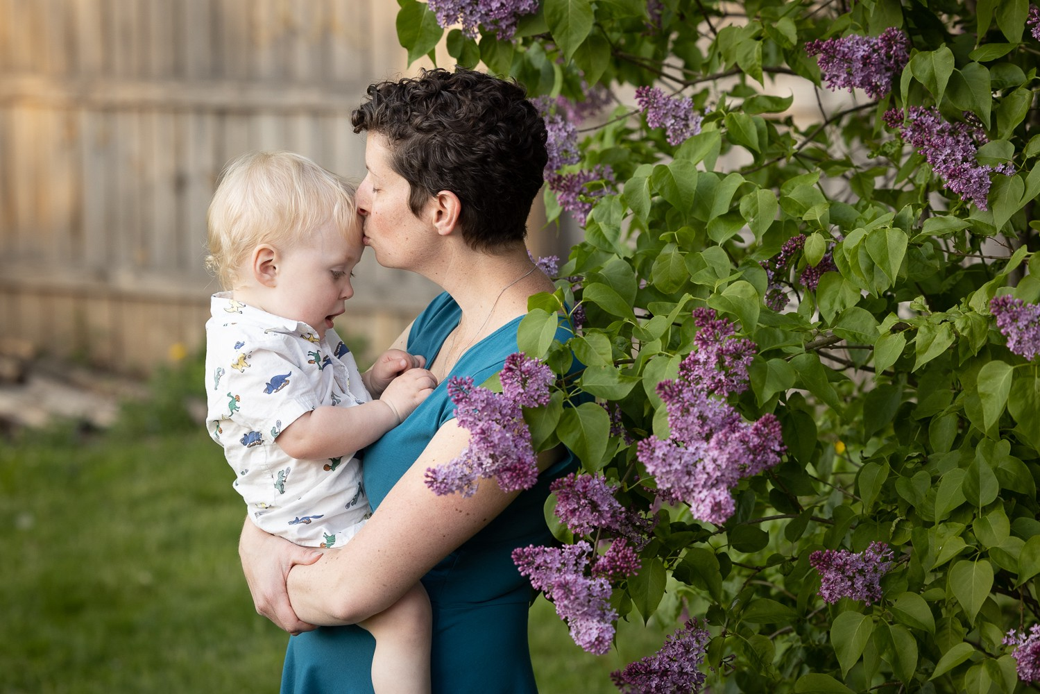 mother kissing boys forehead, standing near purple lilacs