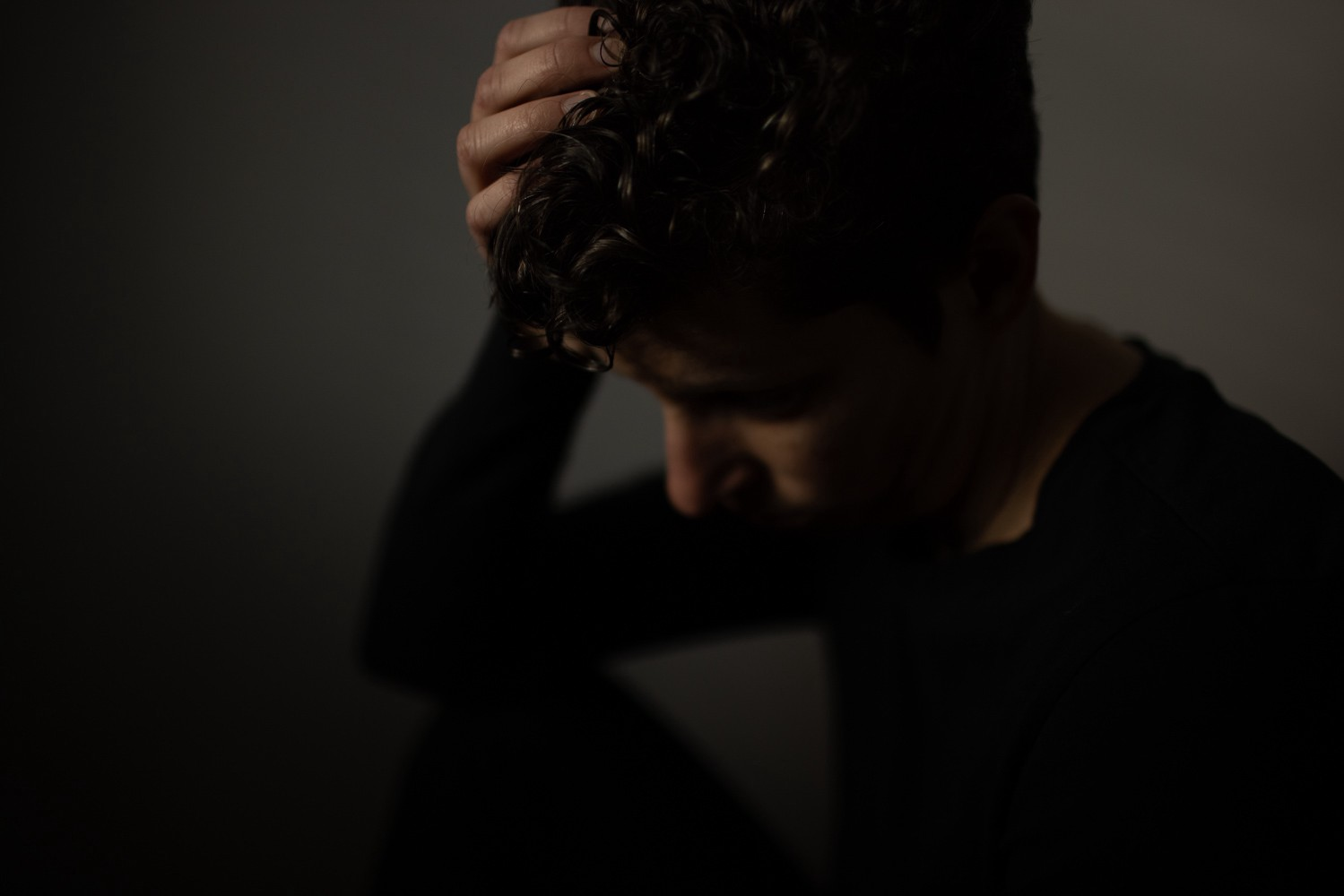 dark moody portrait, face blurred, hand resting on top of head