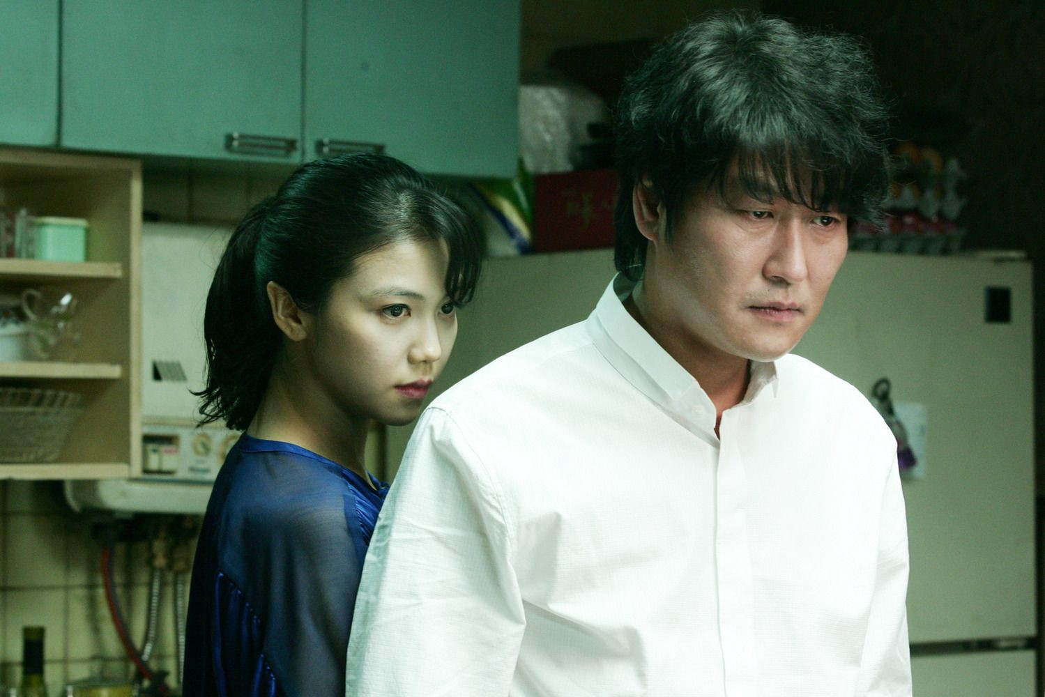 A woman is seen standing behind a man in a kitchen. They are both staring in the same direction.