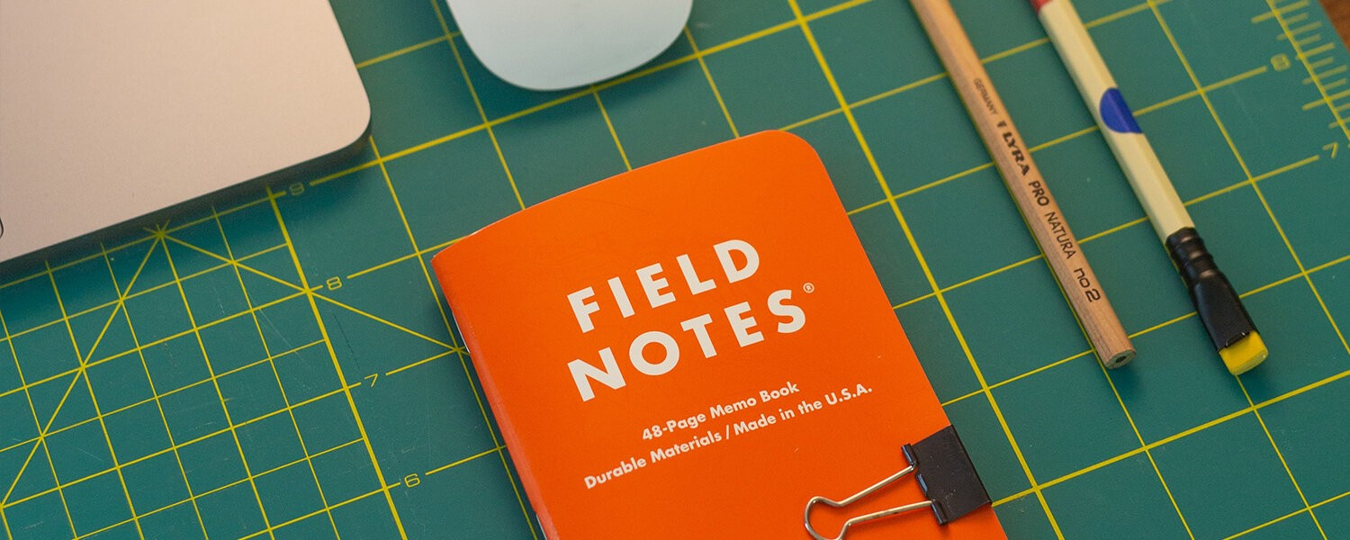 A Field Notes notebook sits with a pencil near a laptop.
