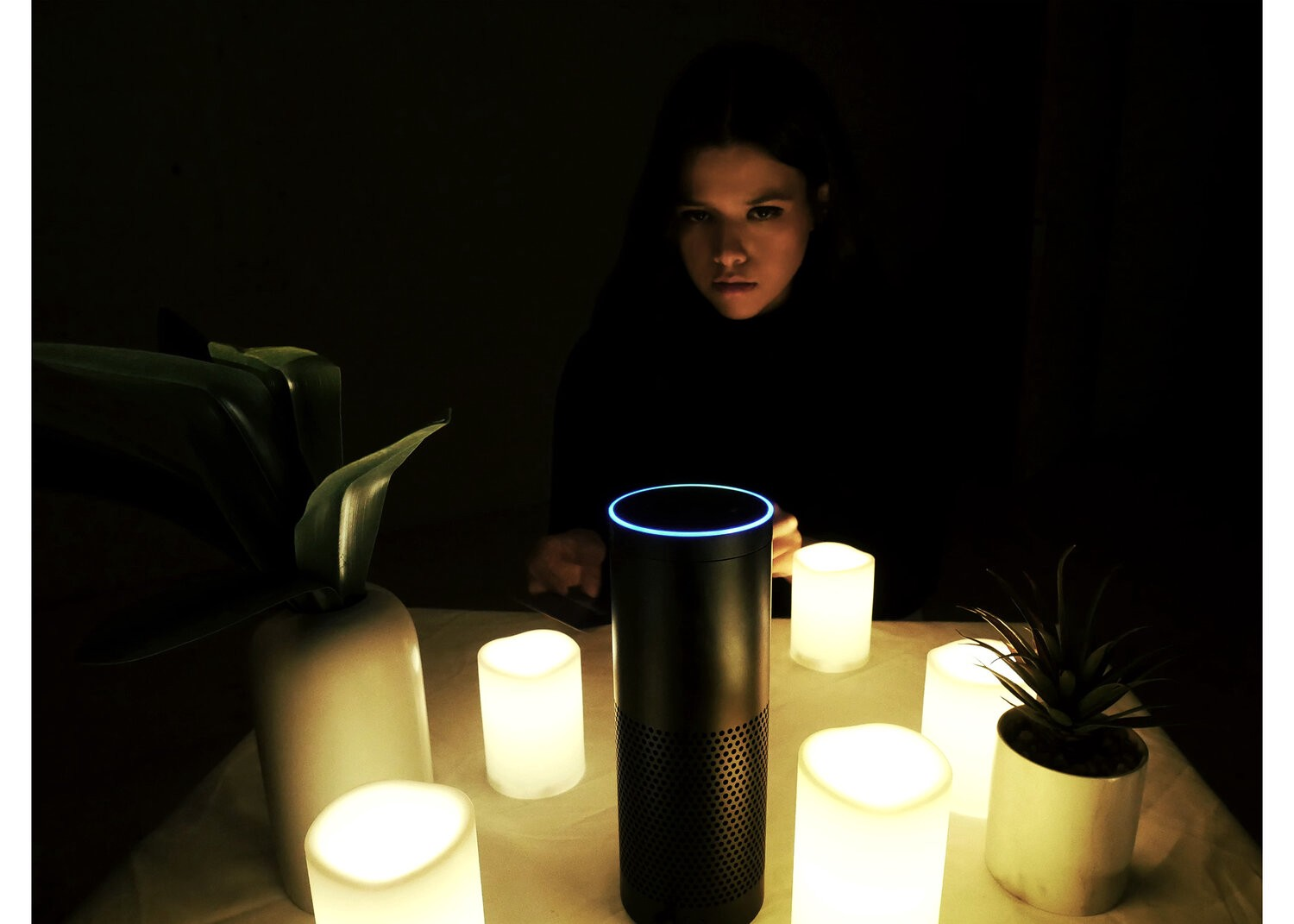 The author sits in the dark behind the Amazon Echo, which is surrounded by lit candles in a seance-style set up.