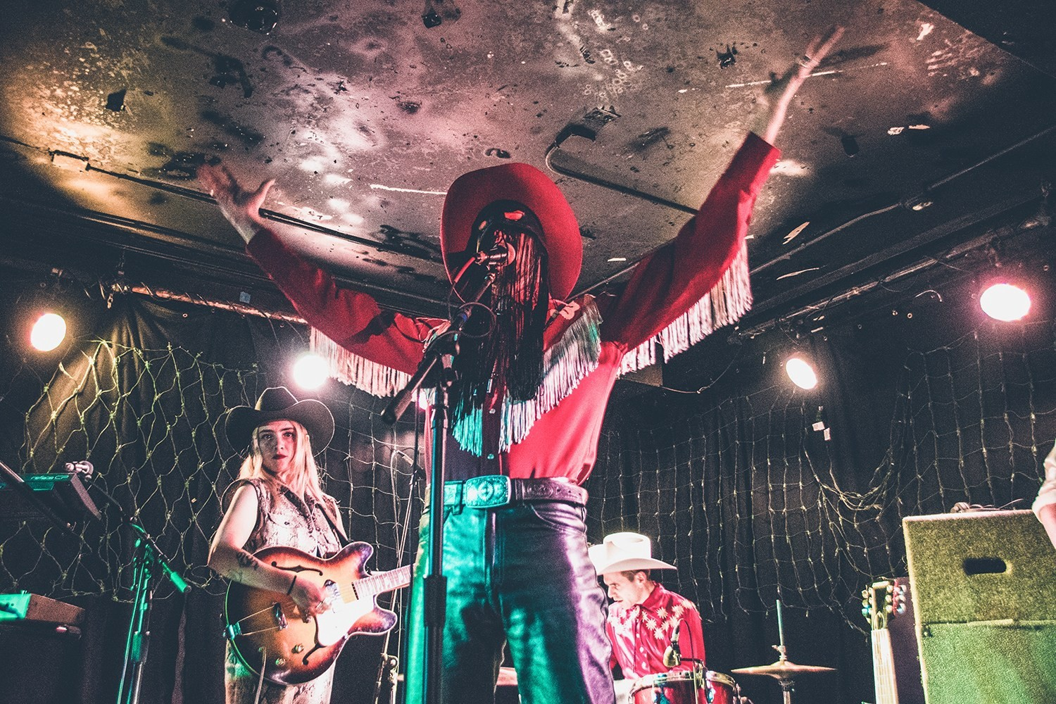 Orville Peck in a red, fringed western costume raises his hand at a live concert.