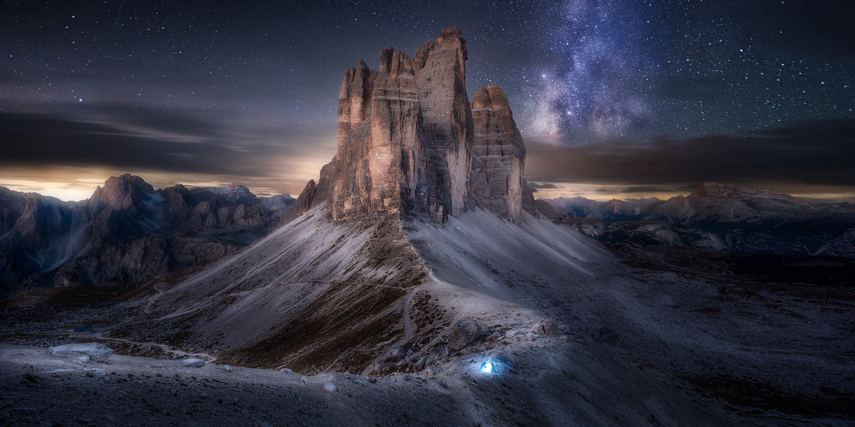 A small range of mountains that looks almost like a castle is backed by a blue/black sky packed with bright white stars