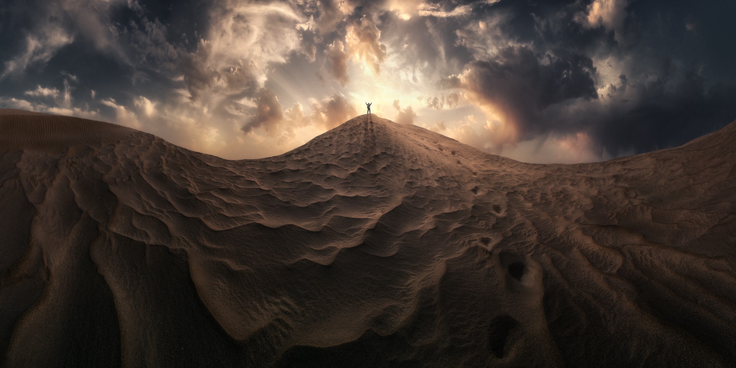 A man stands on top of peak of sand with arms outstretched, backed by a bright sun
