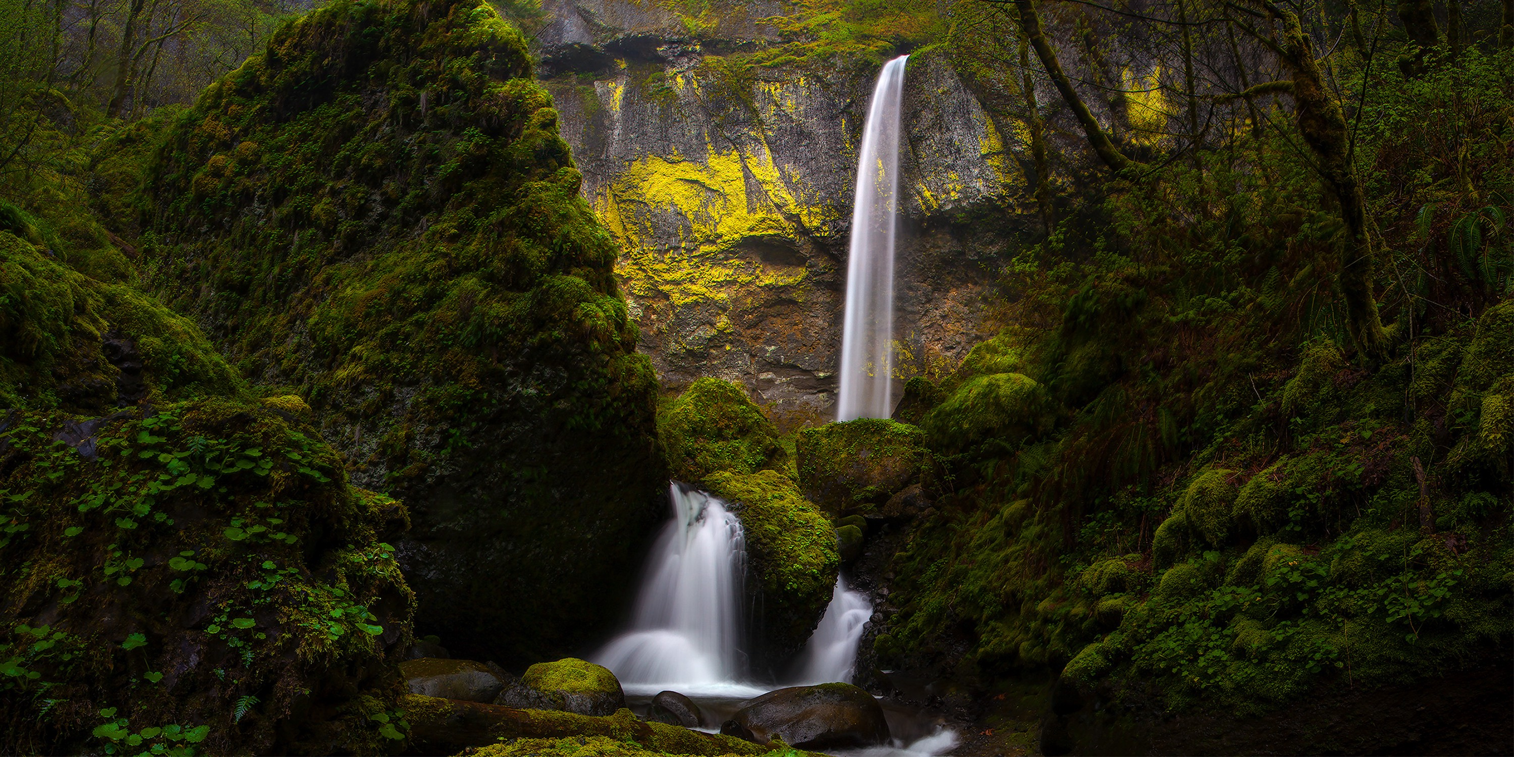Mossy rocks surround a white crystal clear waterfall in multiple tiers