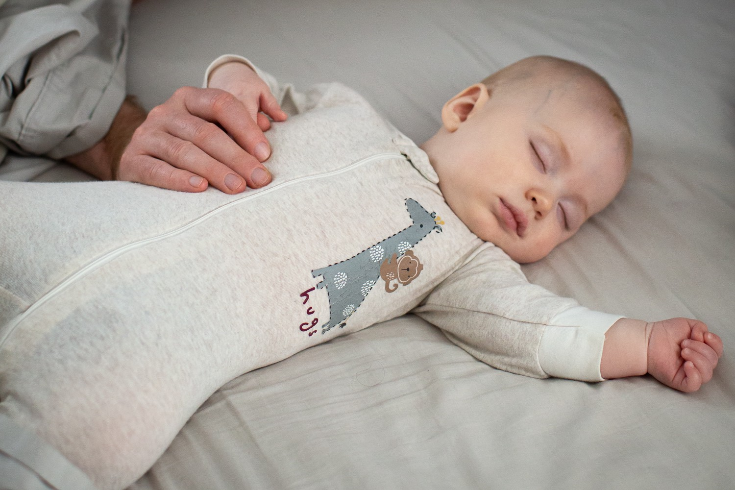 dad holding hands with sleeping baby