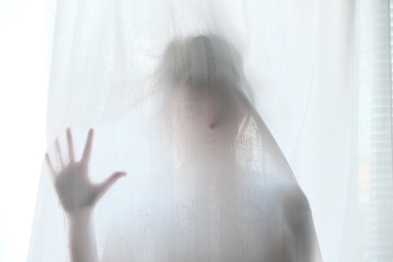 A woman standing behind a white see-through curtain.
