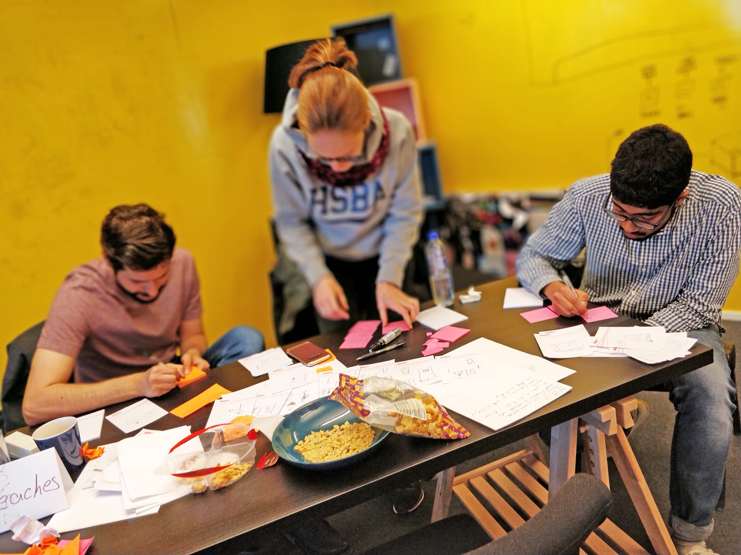 Three students writing on post its. Table is covered with paper, post its, and half-eaten snacks.