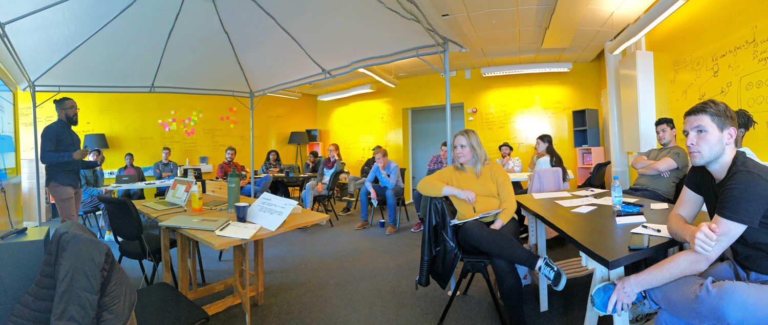 Eduardo presenting under a tent in the yellow room, students seated in a circle or chairs around him.