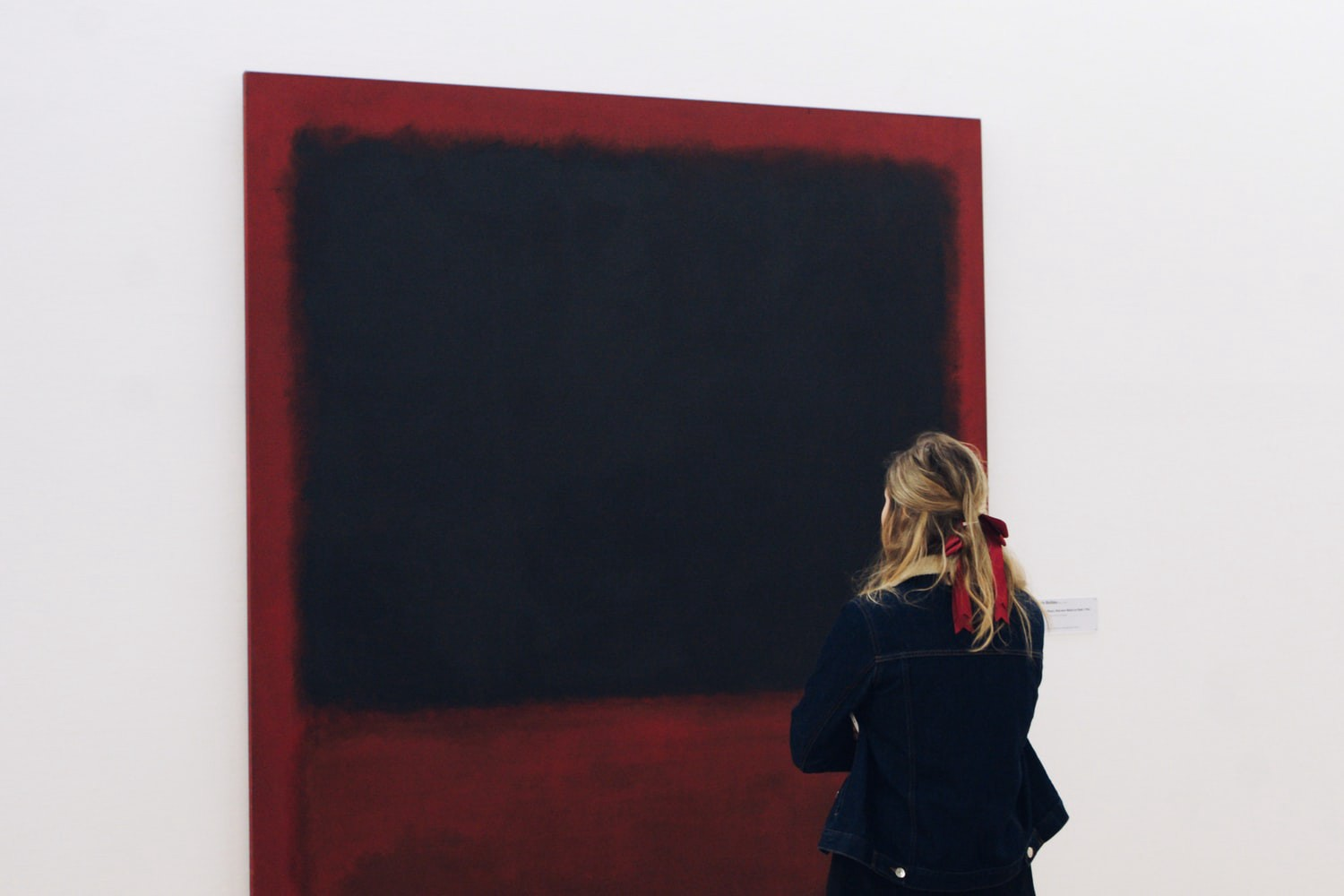 Woman staring at painting in a museum.