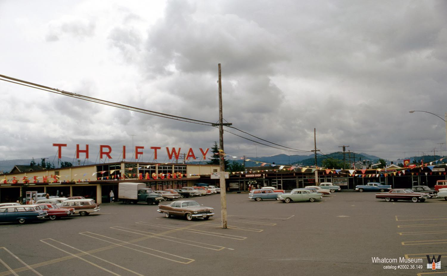 parking lot of cars and supermarket in the background