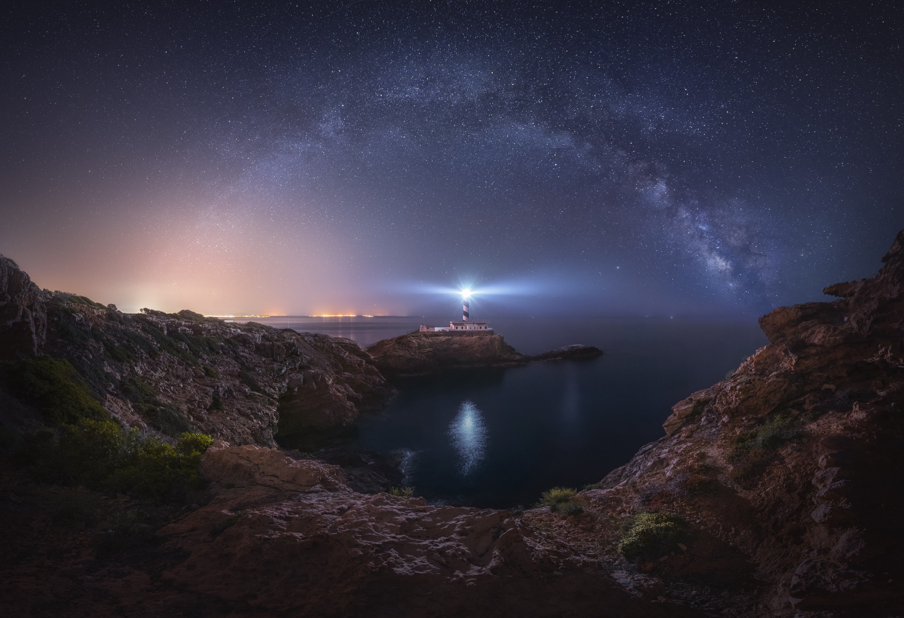 A small striped lighthouse shines a bright light over a rocky, dark ocean cove, with a very starry night sky shown above