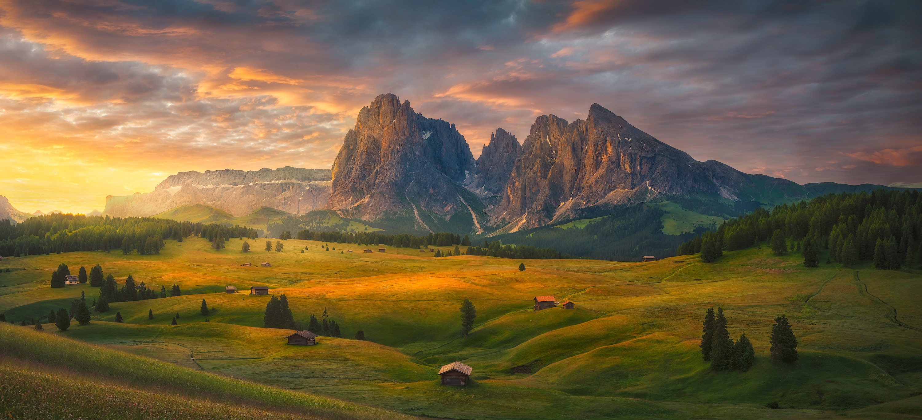 The sunrises over a valley in Italy, backed by a beautiful mountain and dotted with charming, small houses