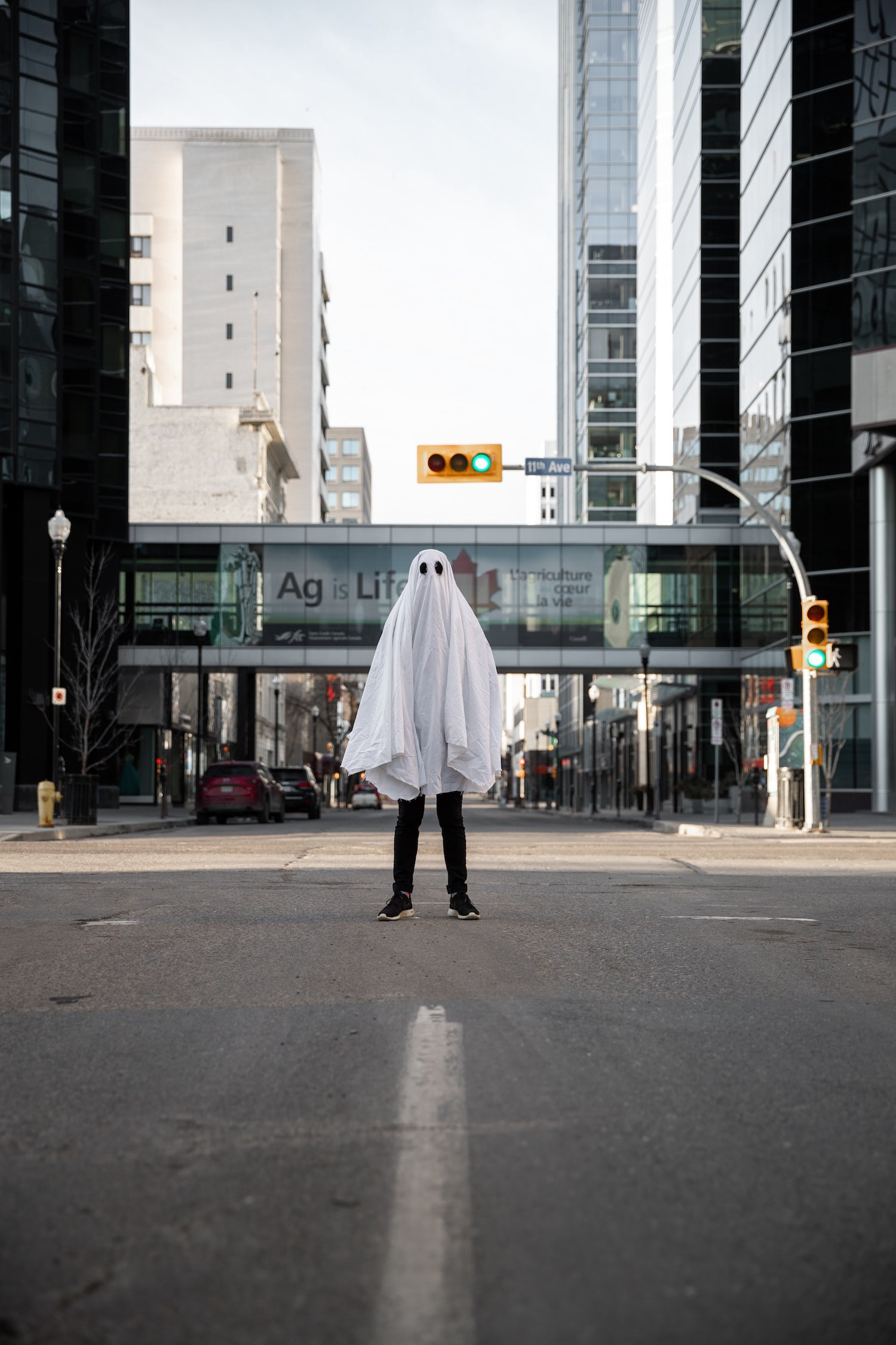 Man standing in road in ghost costume.