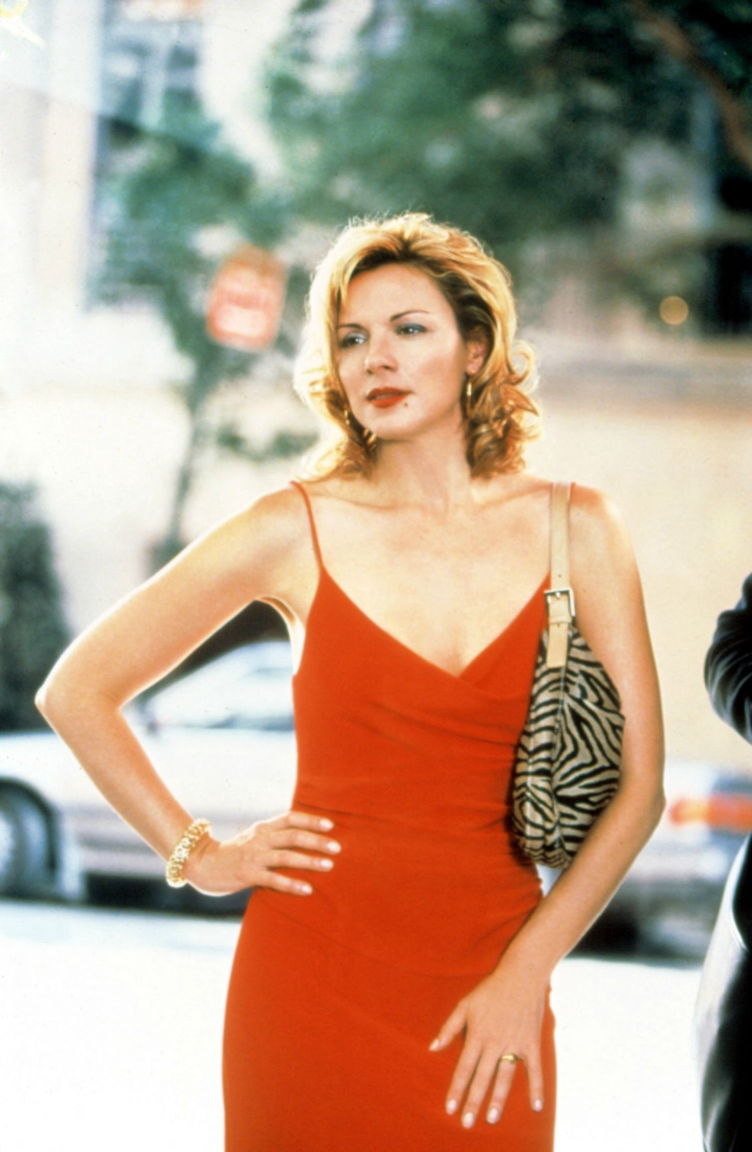 Still of Kim Cattrall as Samantha Jones in a red dress and sexy, confident pose from Sex and the City's fourth season