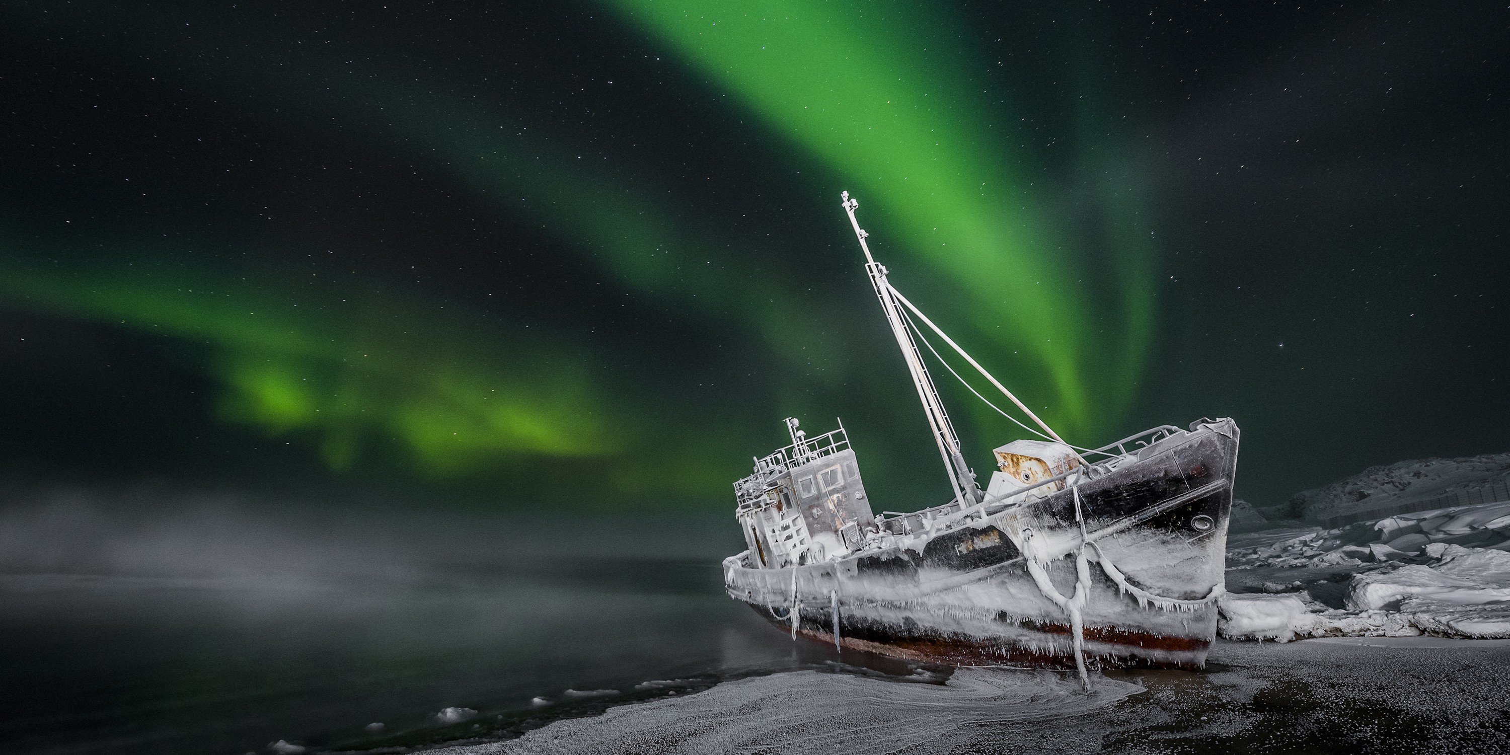 A fine art photograph of a crashed ship backed by a green and black sky with northern lights