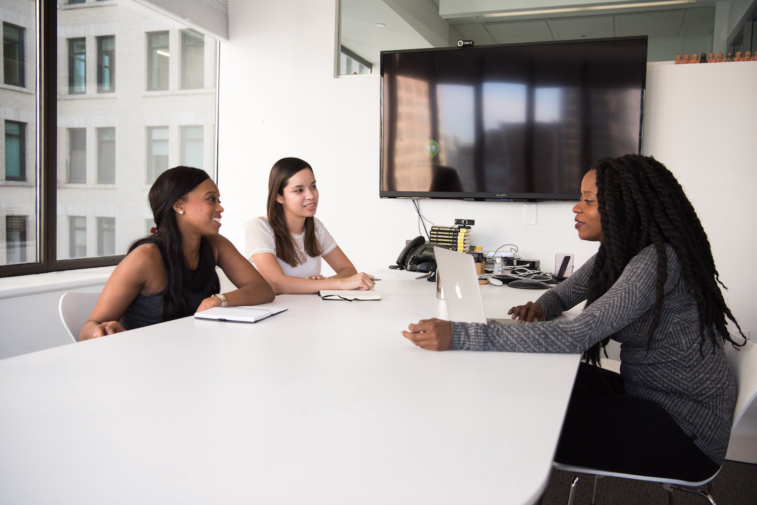 Three ladies sit around a desk with a laptop to discuss work in a bright office room