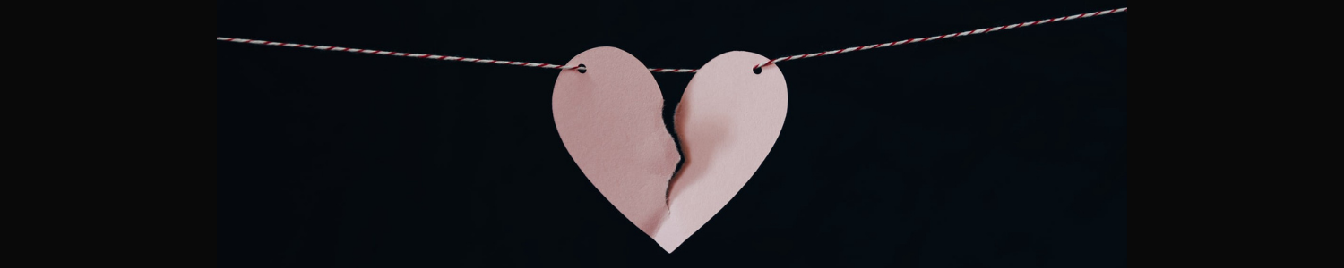 A ripped paper heart hanging on a string against a black background.