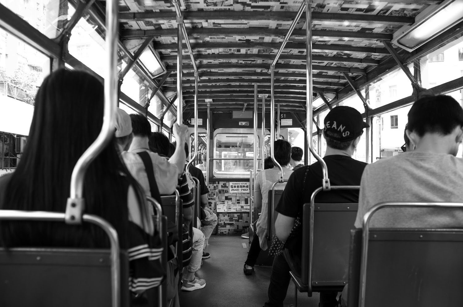 Riders on the Hong Kong tram in black and white