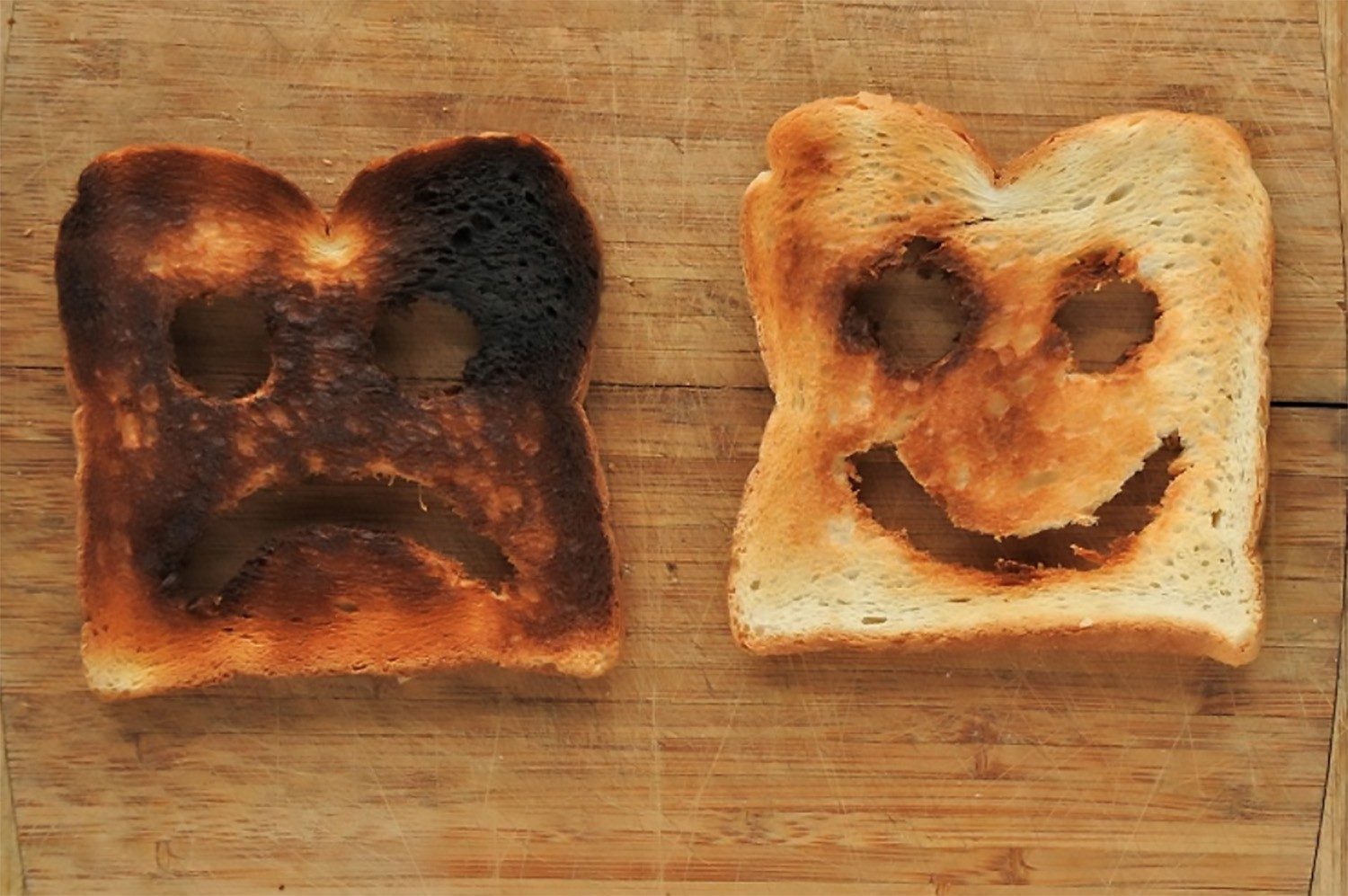 burned slice of toast looking sad next to perfectly toasted slice looking happy