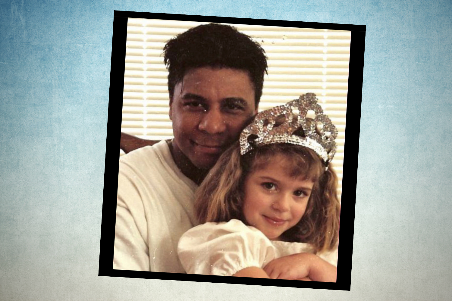 A Polaroid-looking portrait of a Black man with short hair hugging a child with shoulder-length hair and wearing a tiara.