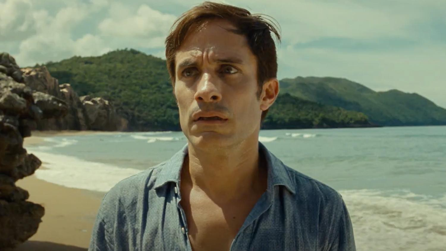 A man stares in disbelief on a beach.