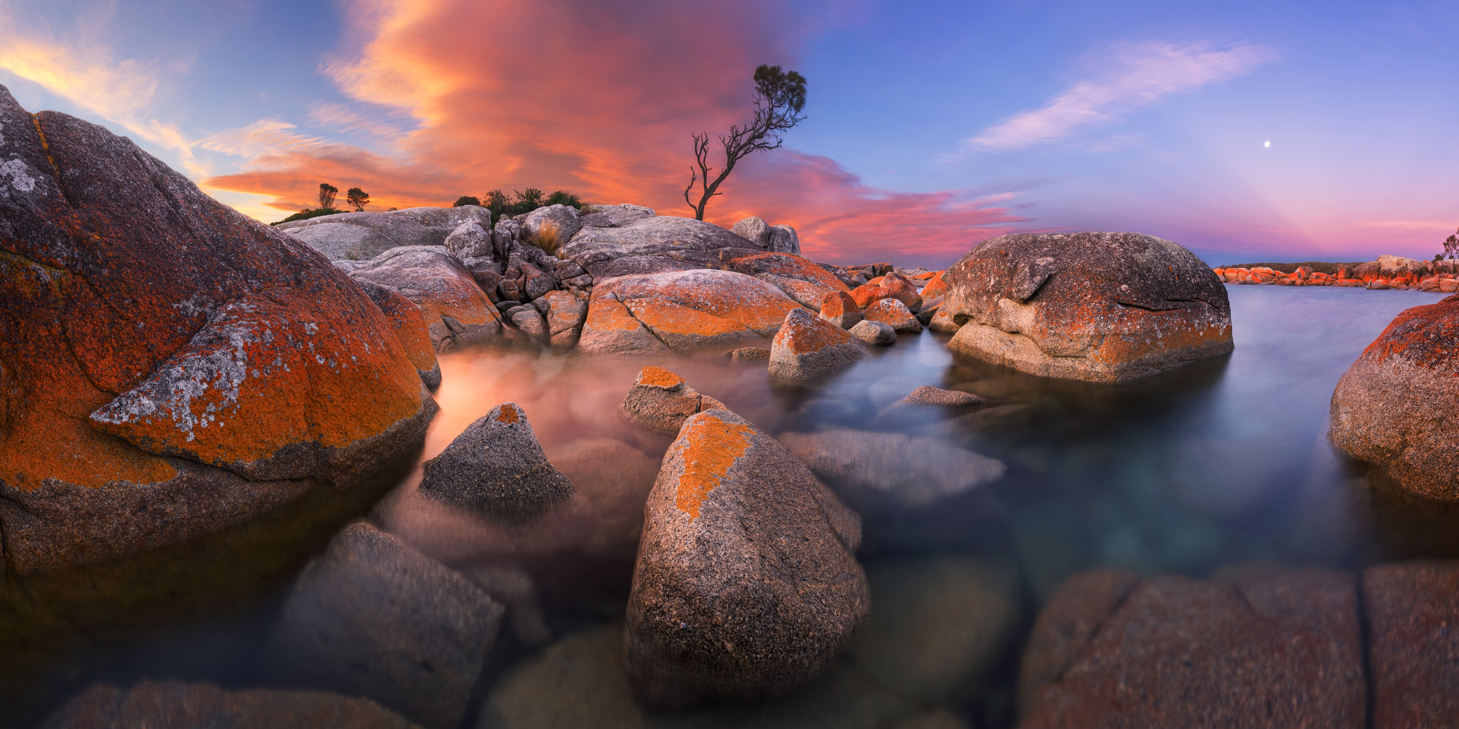 A sunset bathes rocks and water in orange and lavender light