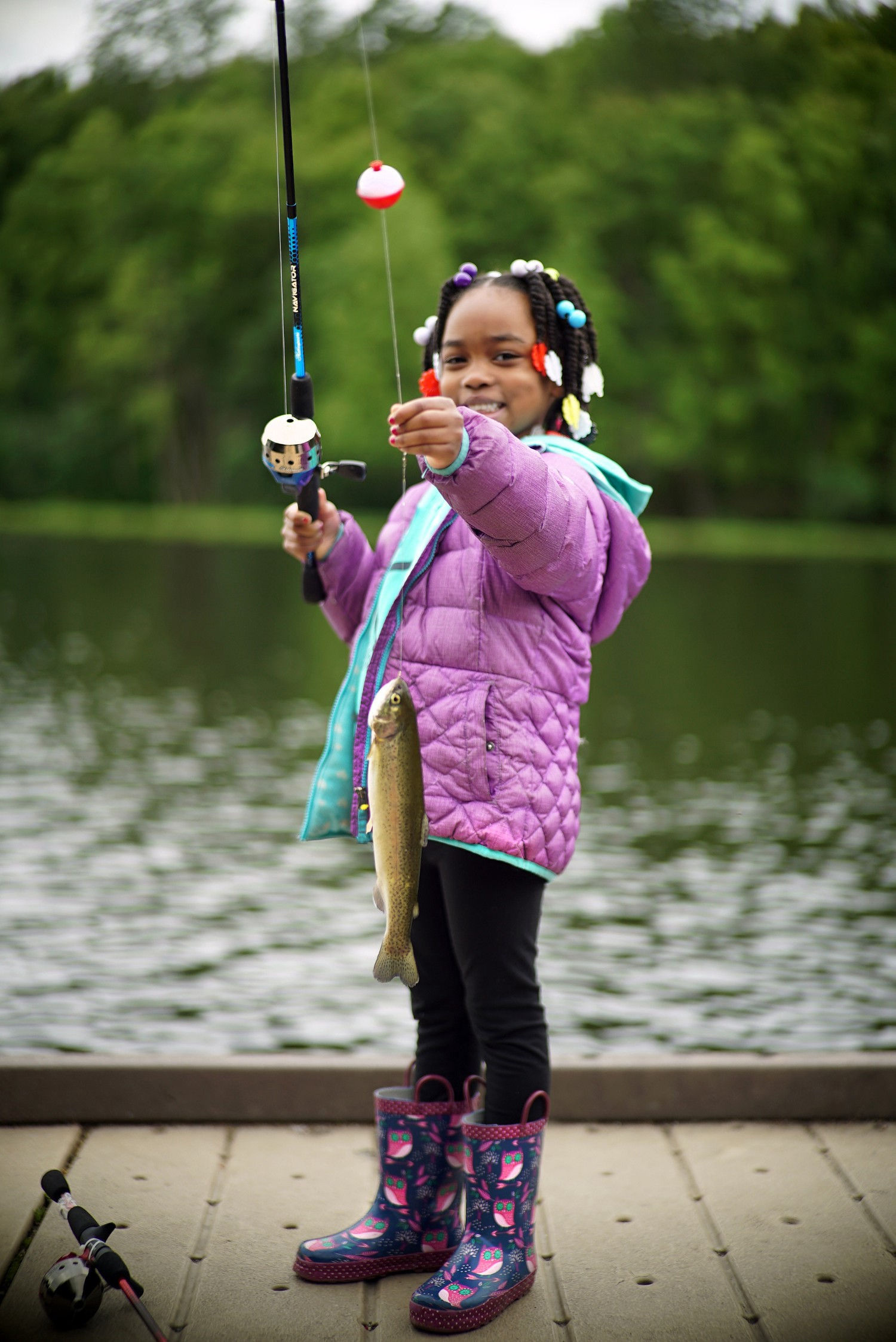 young girl holding a trout by a lake