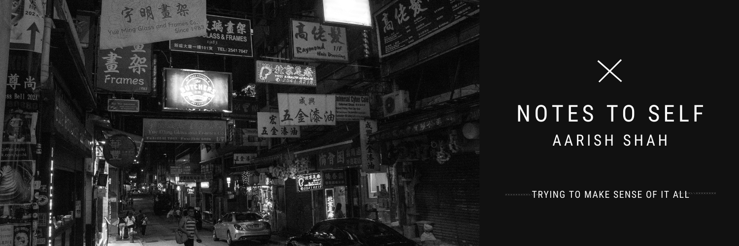 Night time shot of Hong Kong street, with the street signs hanging everywhere over an empty street with one passer by.