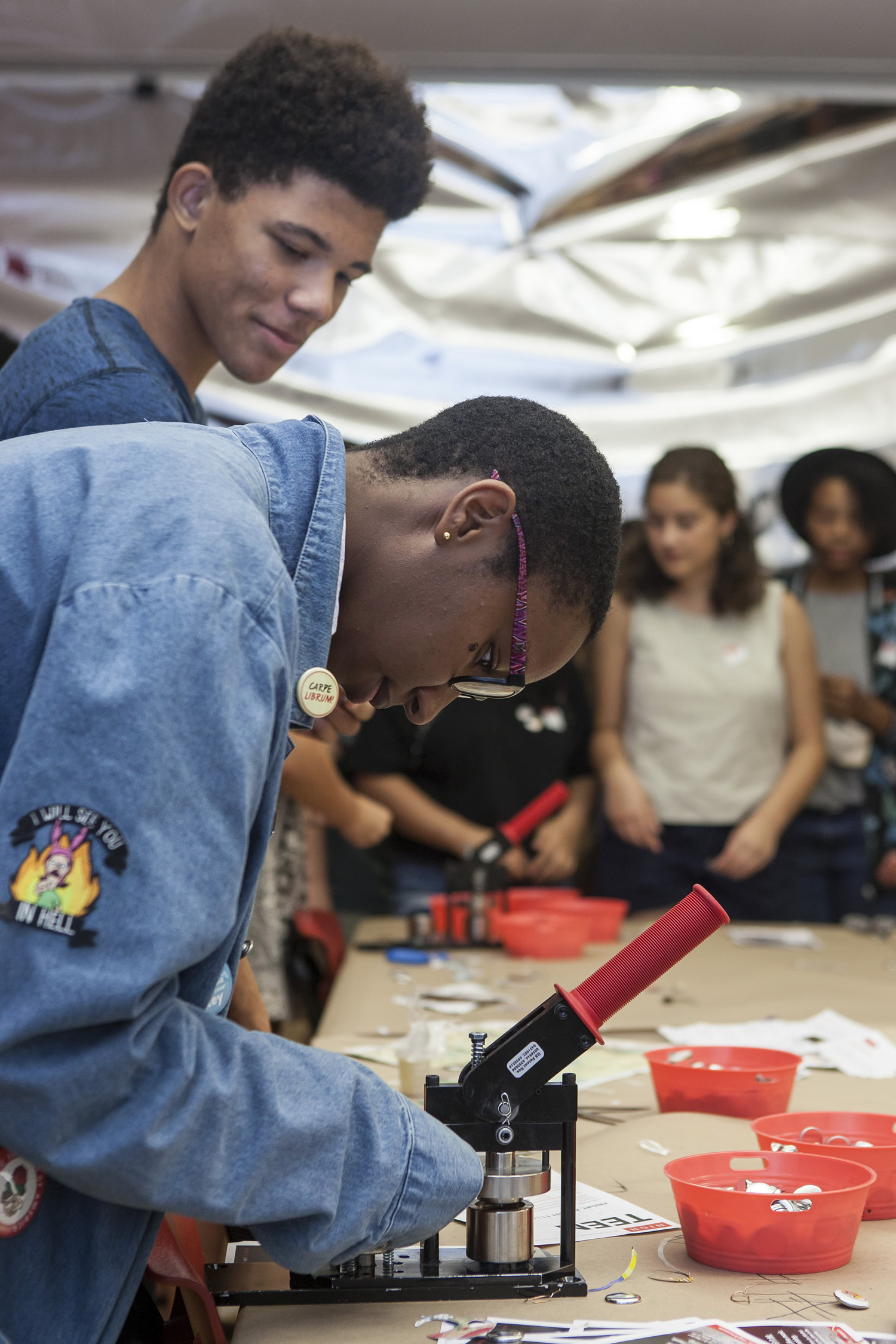 A teen uses a machine to make buttons while other teens look on.