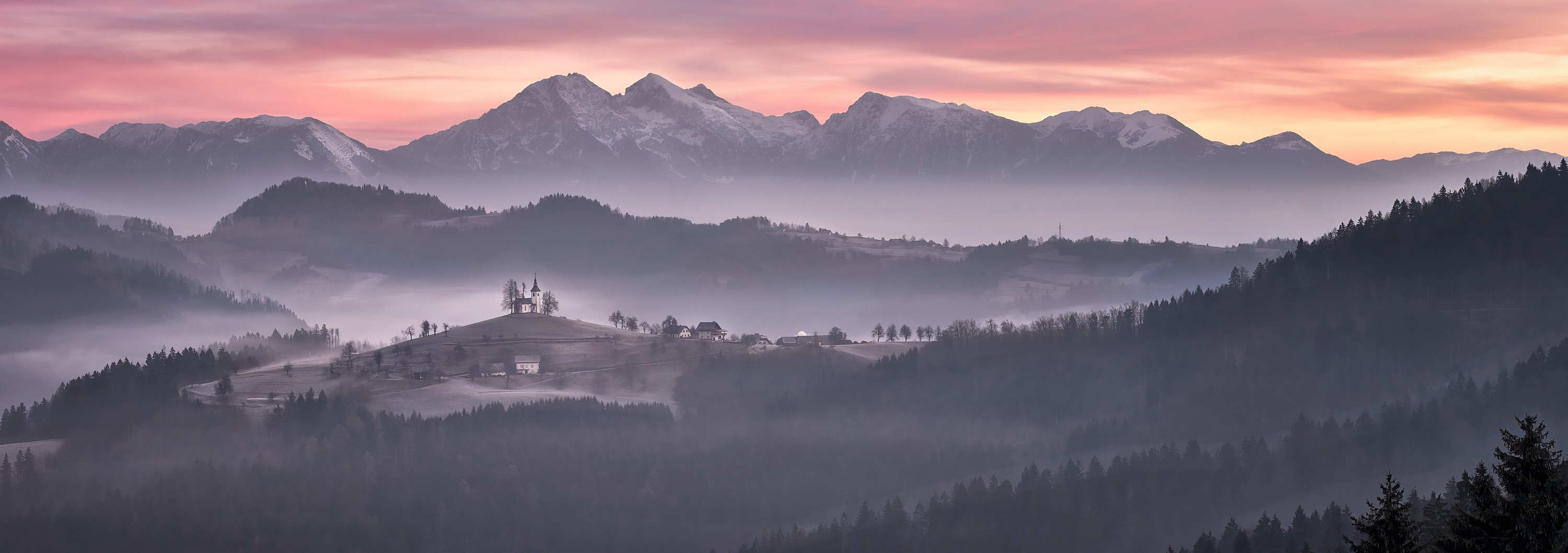 A fine art photograph of a pastel pink and orange sunrise over a range of purple mountains