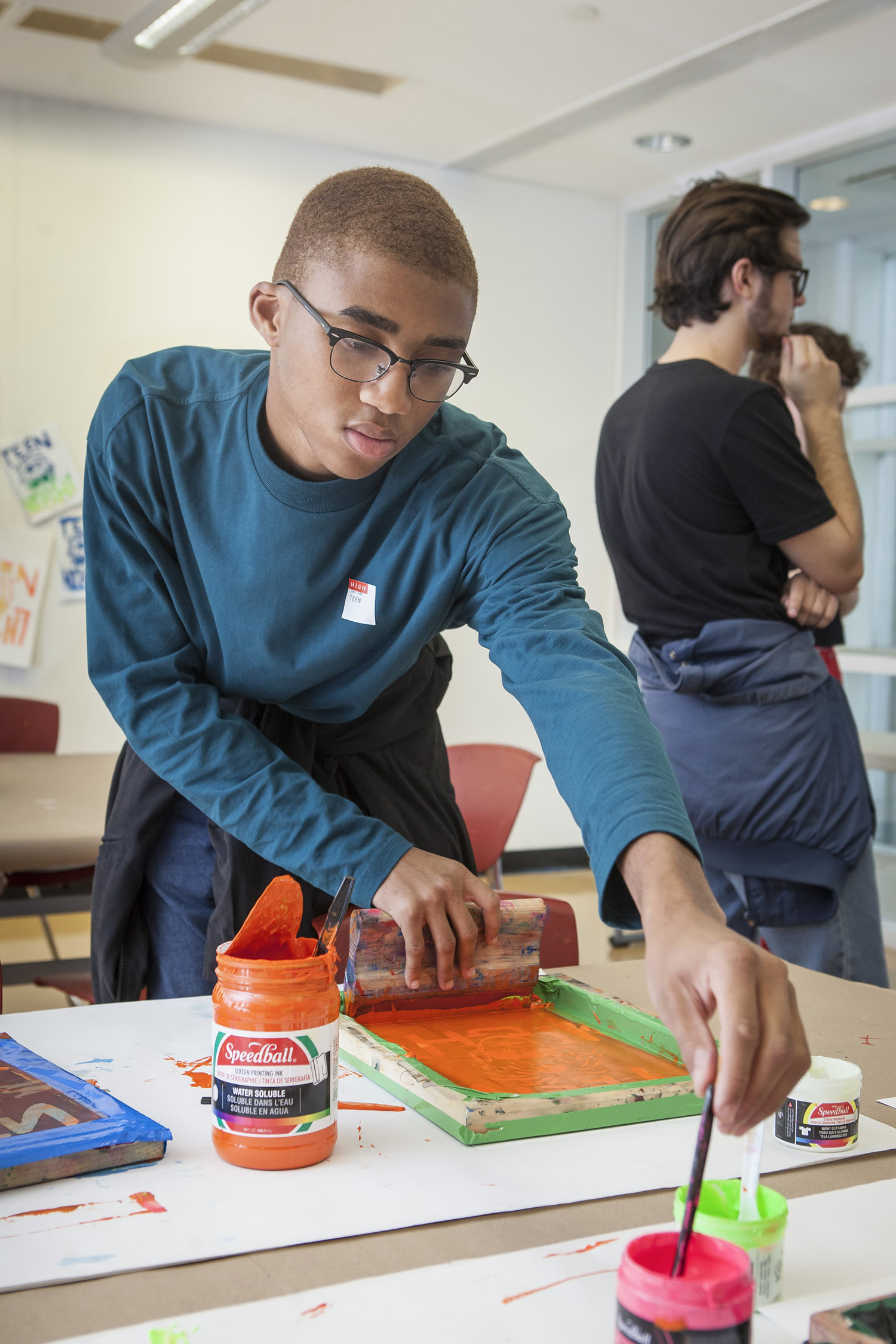 A teenaged boy tries screenprinting in a workshop at the High Museum of Art.