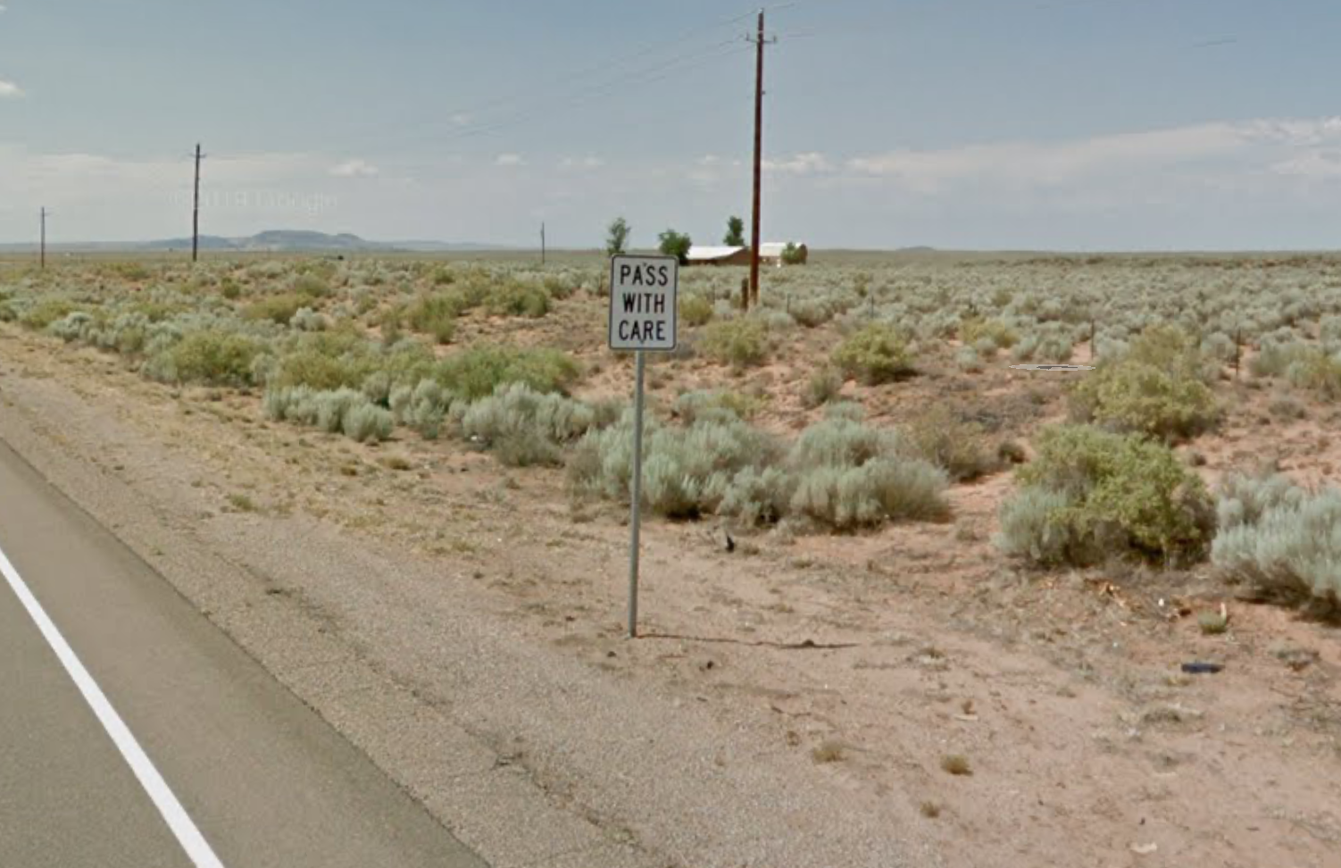 """A """"pass with care"""" road sign on the east side of New Mexico State Road 47 as you head north"""
