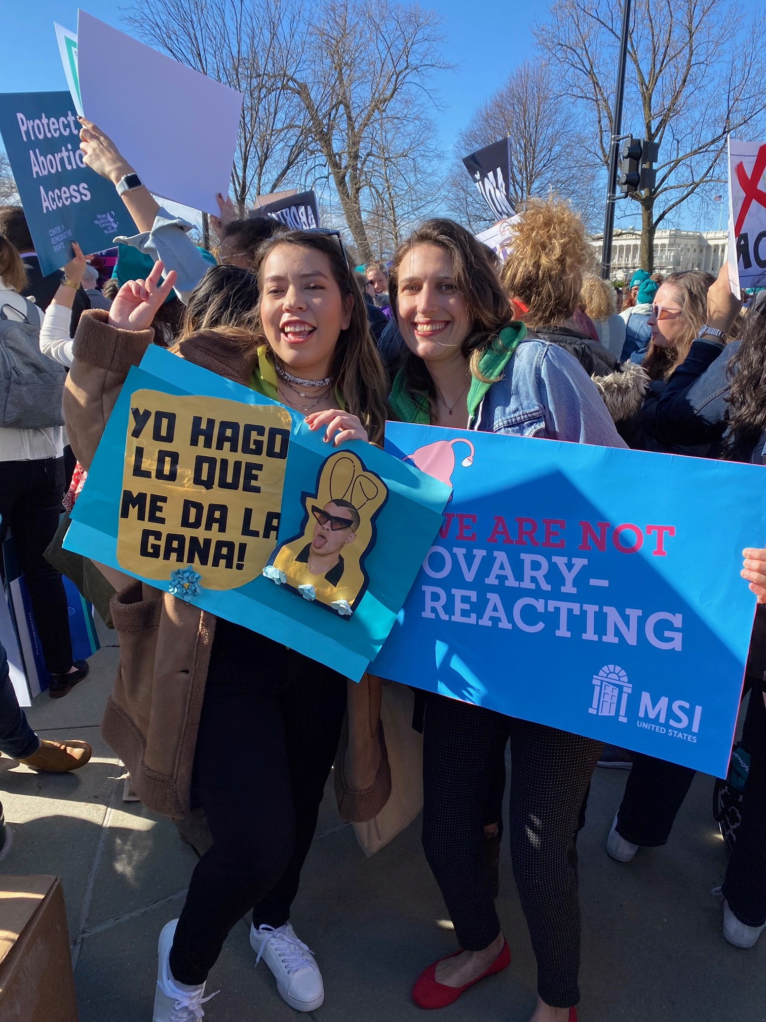 Two women holding pro-choice signs, one in Spanish and the other in English.