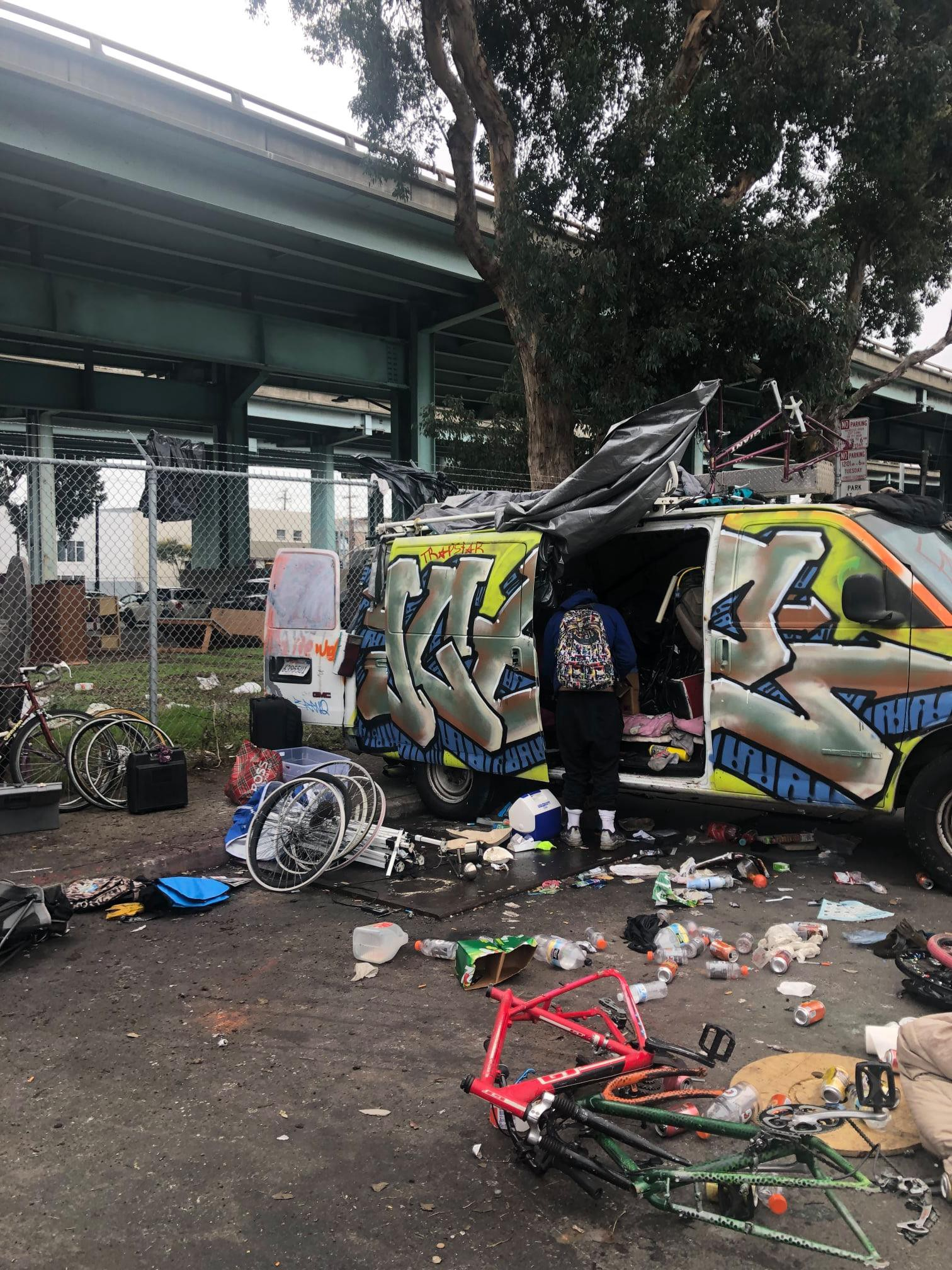 A figure stands in the open door of a gratified van, surrounded by bike parts, a cooler, and other supplies