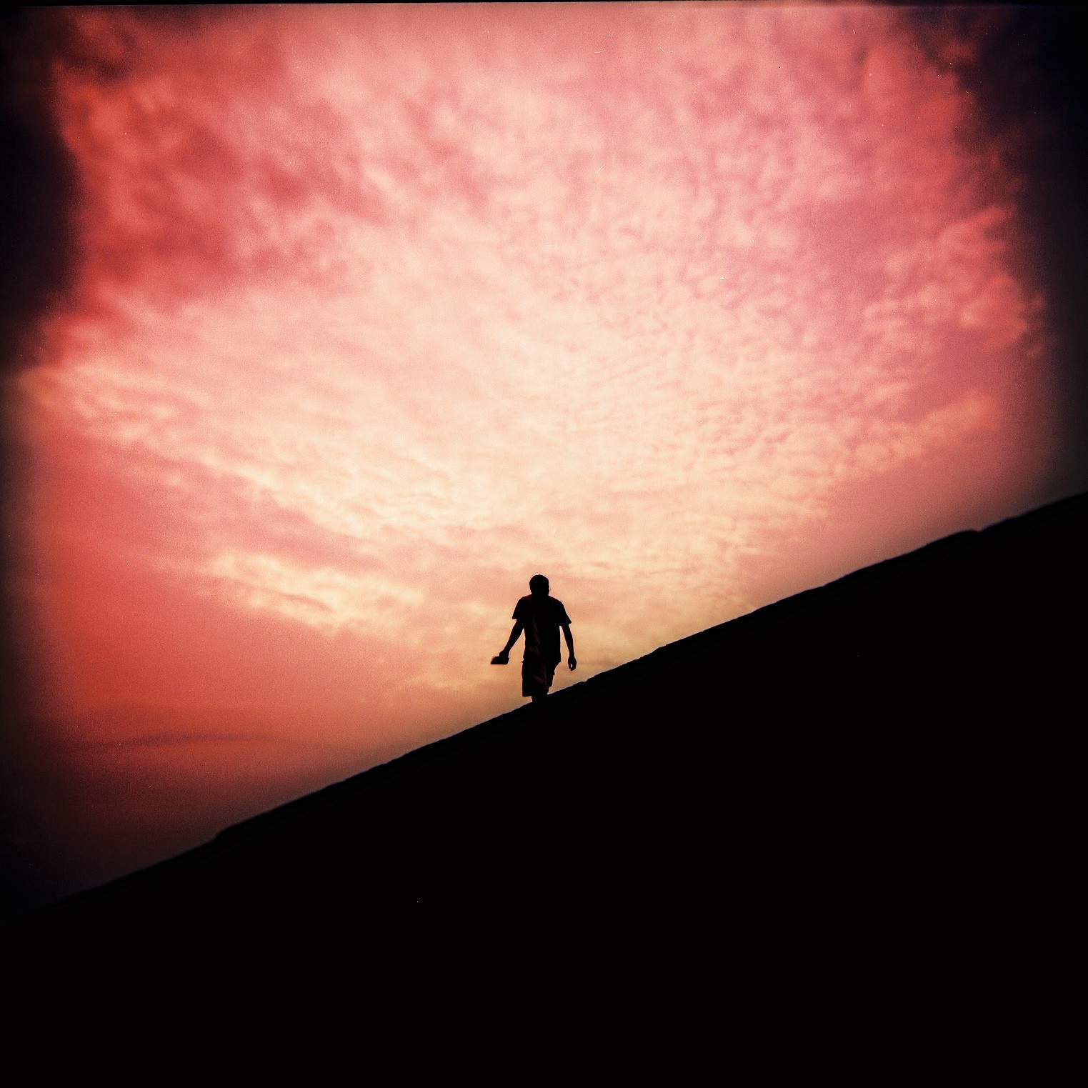 Photo of the dark silhouette of a person walking in front of a pink sunset.