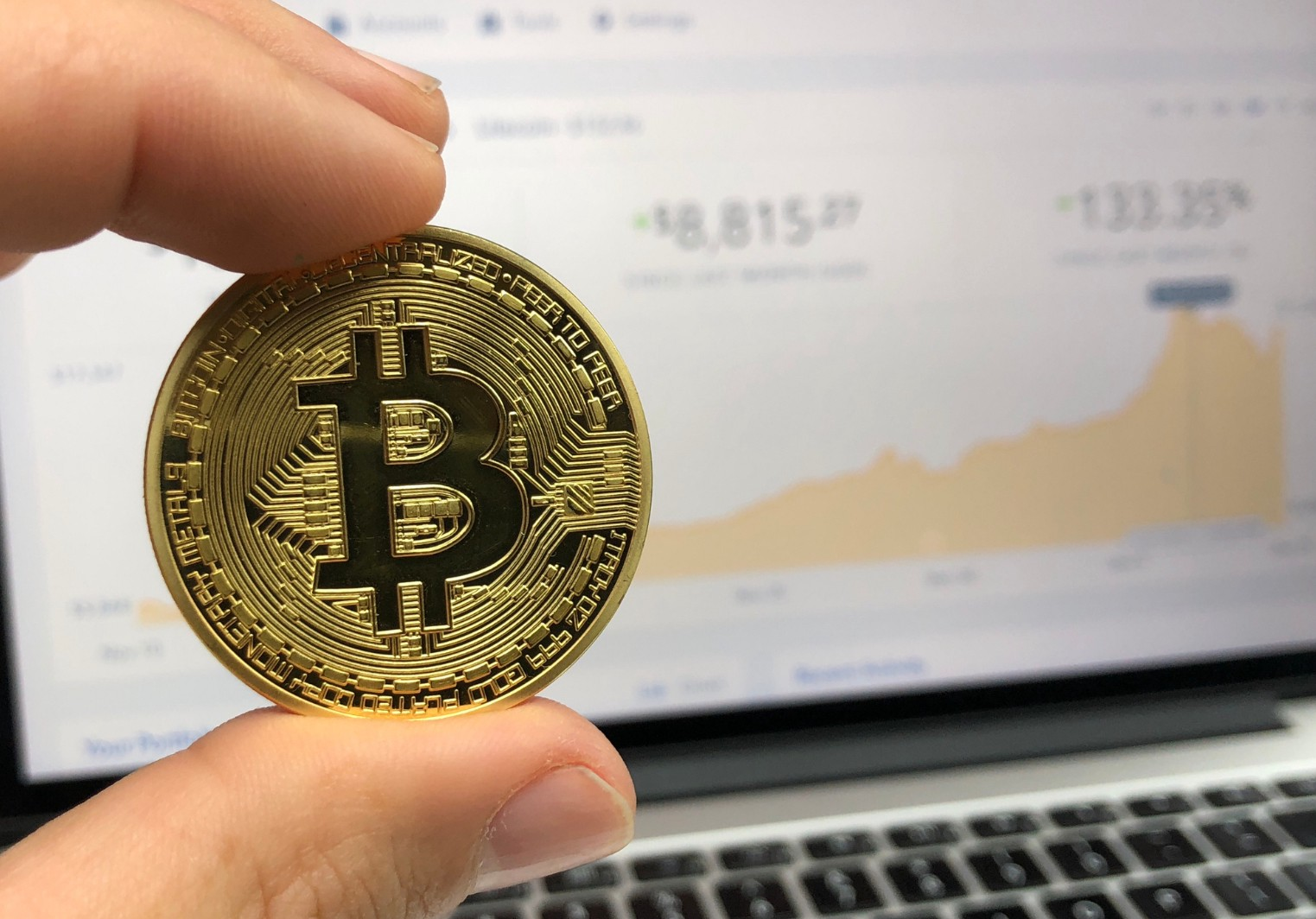 An imagined Bitcoin held in front of a cryptocurrency trading graph