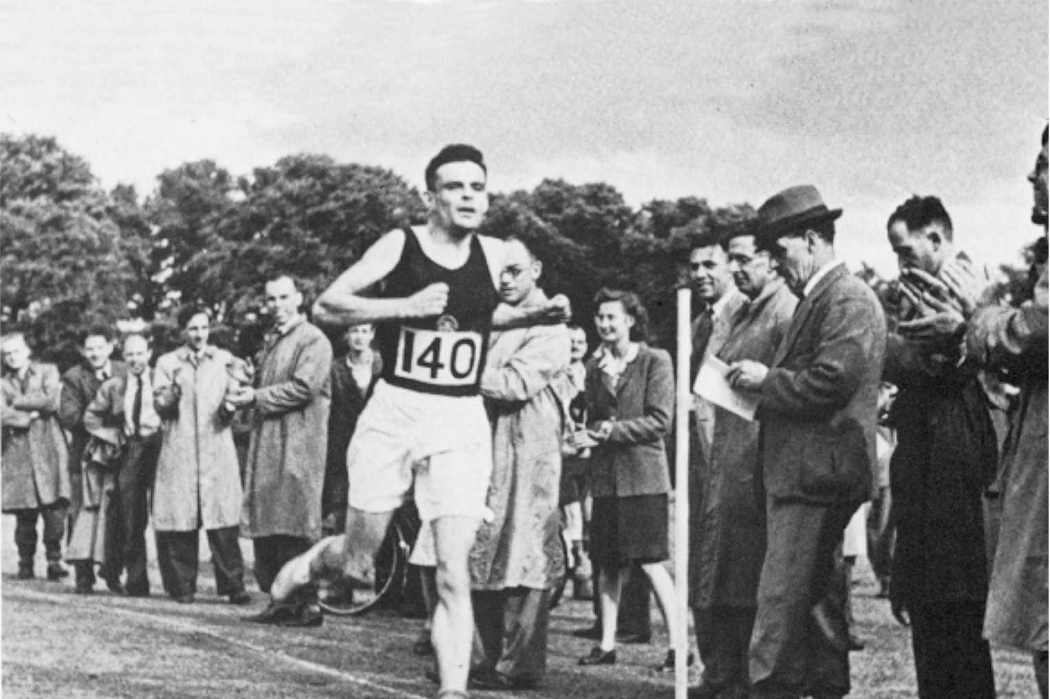 Alan Turing running in front of a crowd, wearing a paper racing number 140
