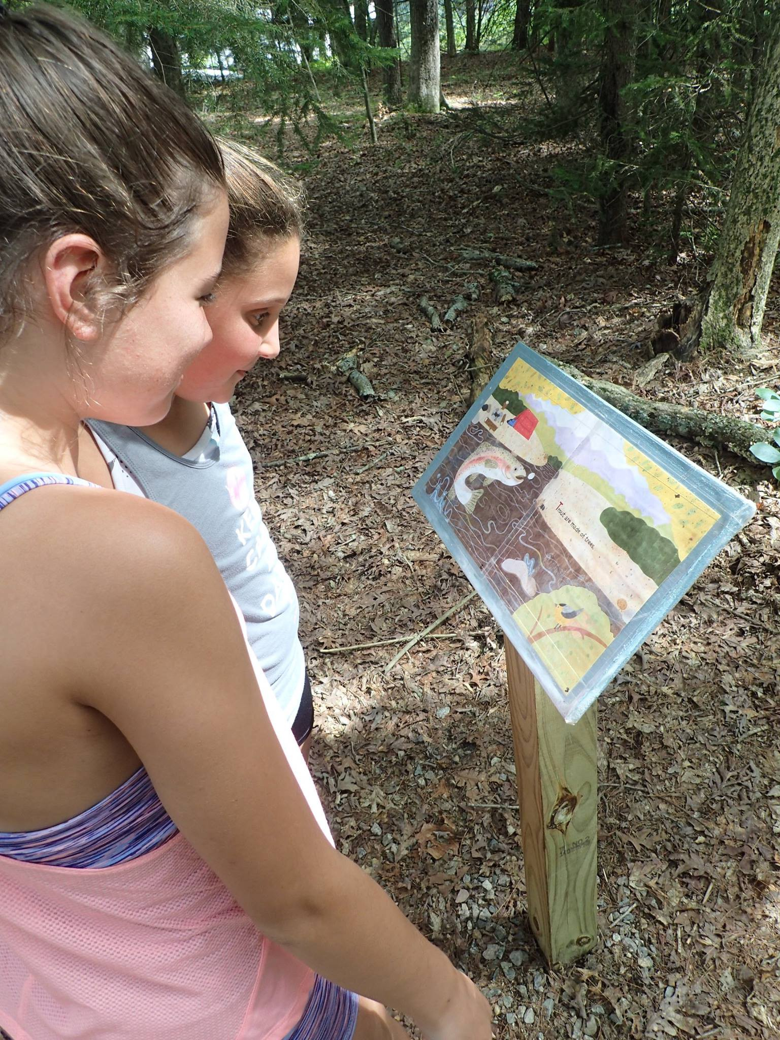 people read interpretive sign on a trail