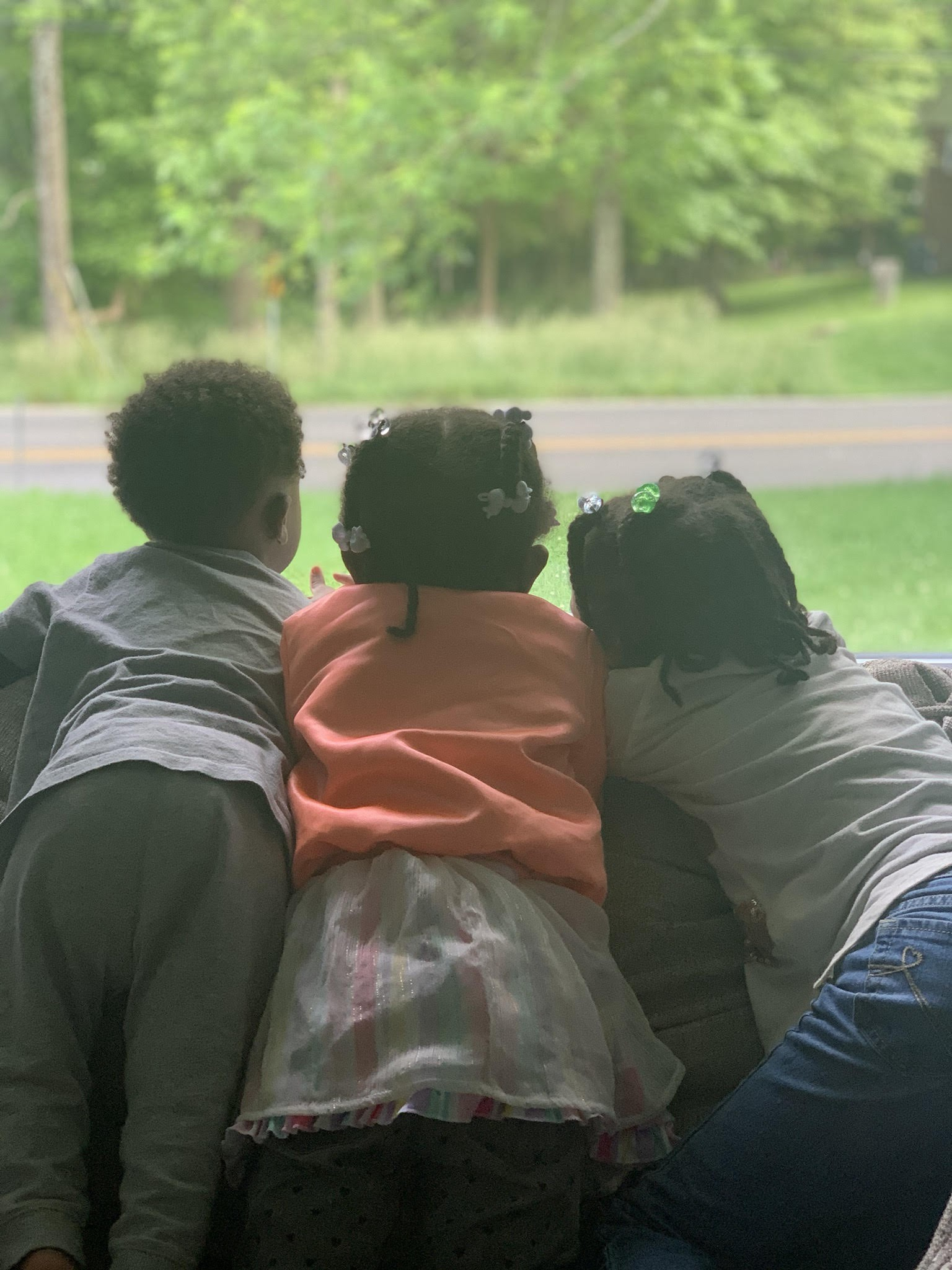 3 young Black children seen from behind, looking out the window at grass and a road.