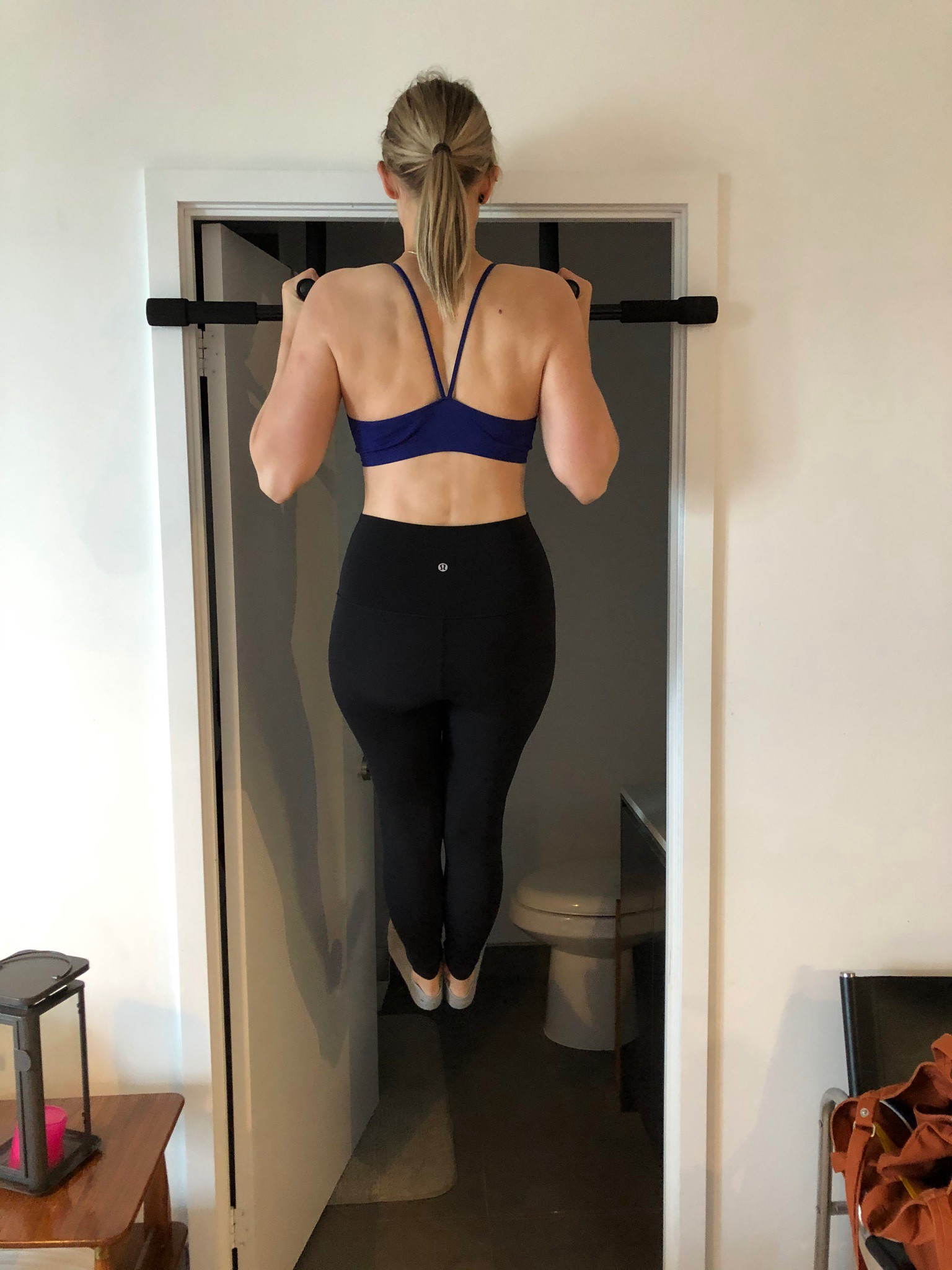 Linn doing a neutral grip flexed arm hang on a chin up bar in a door frame. She is wearing black leggings and purple sports bra.