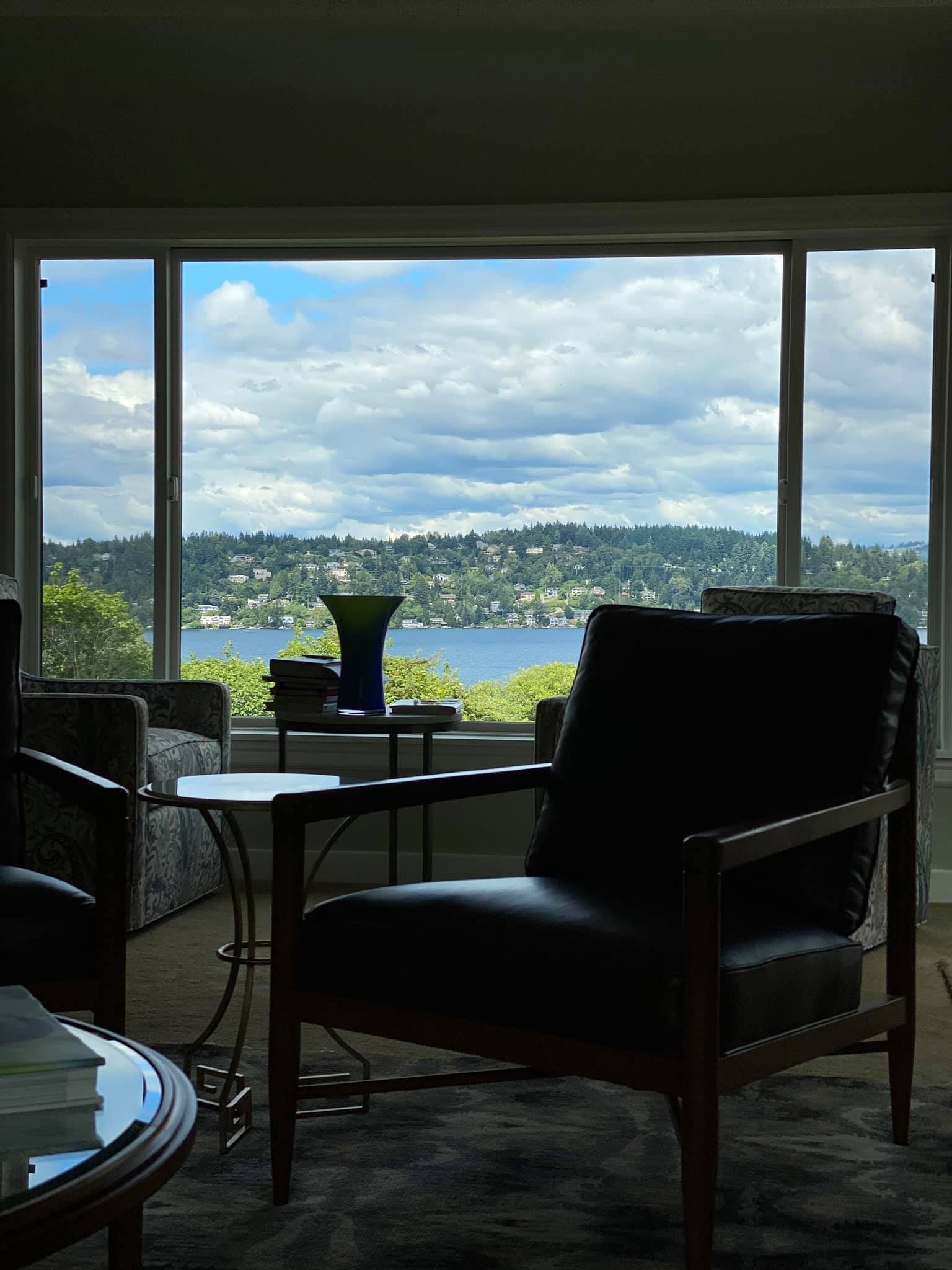 View out the window of a house overlooking Lake Washington with various furniture in shadowed view.