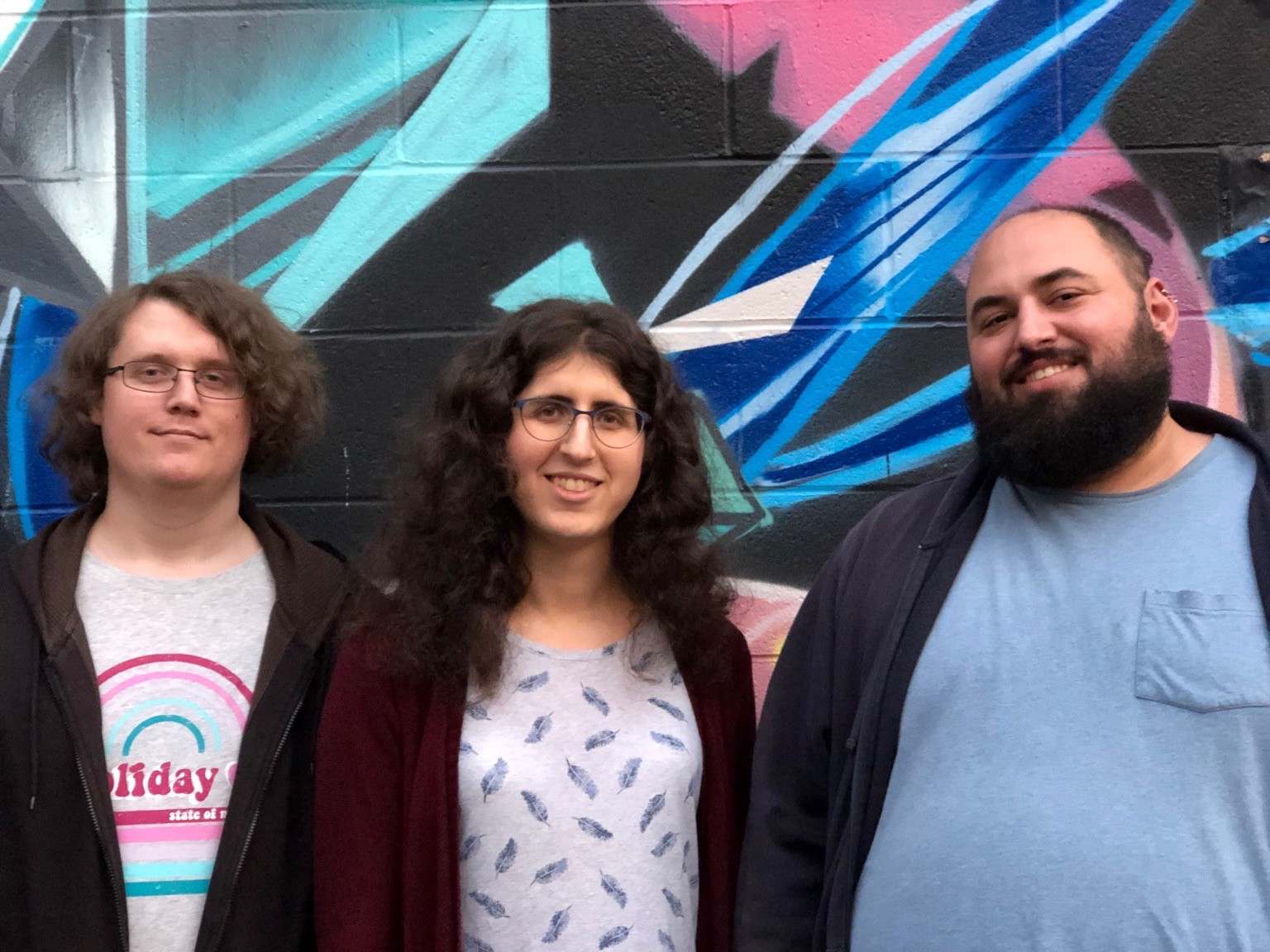 Three of the fired Google organizers standing against a colorful backdrop.