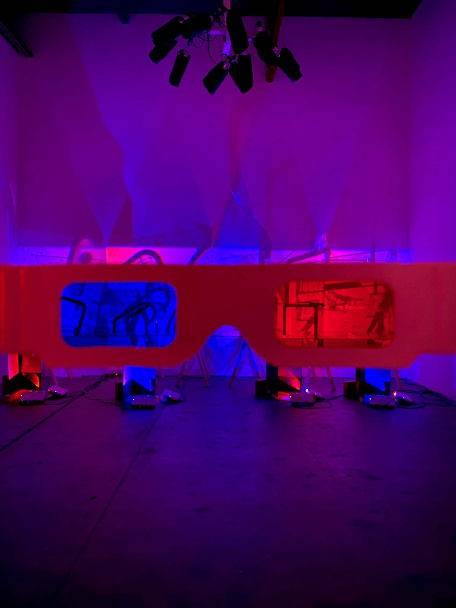 3D glasses held up in front of a piece of light artwork that becomes a stereoscopic image, part of EDGE OF LIGHT exhibition.