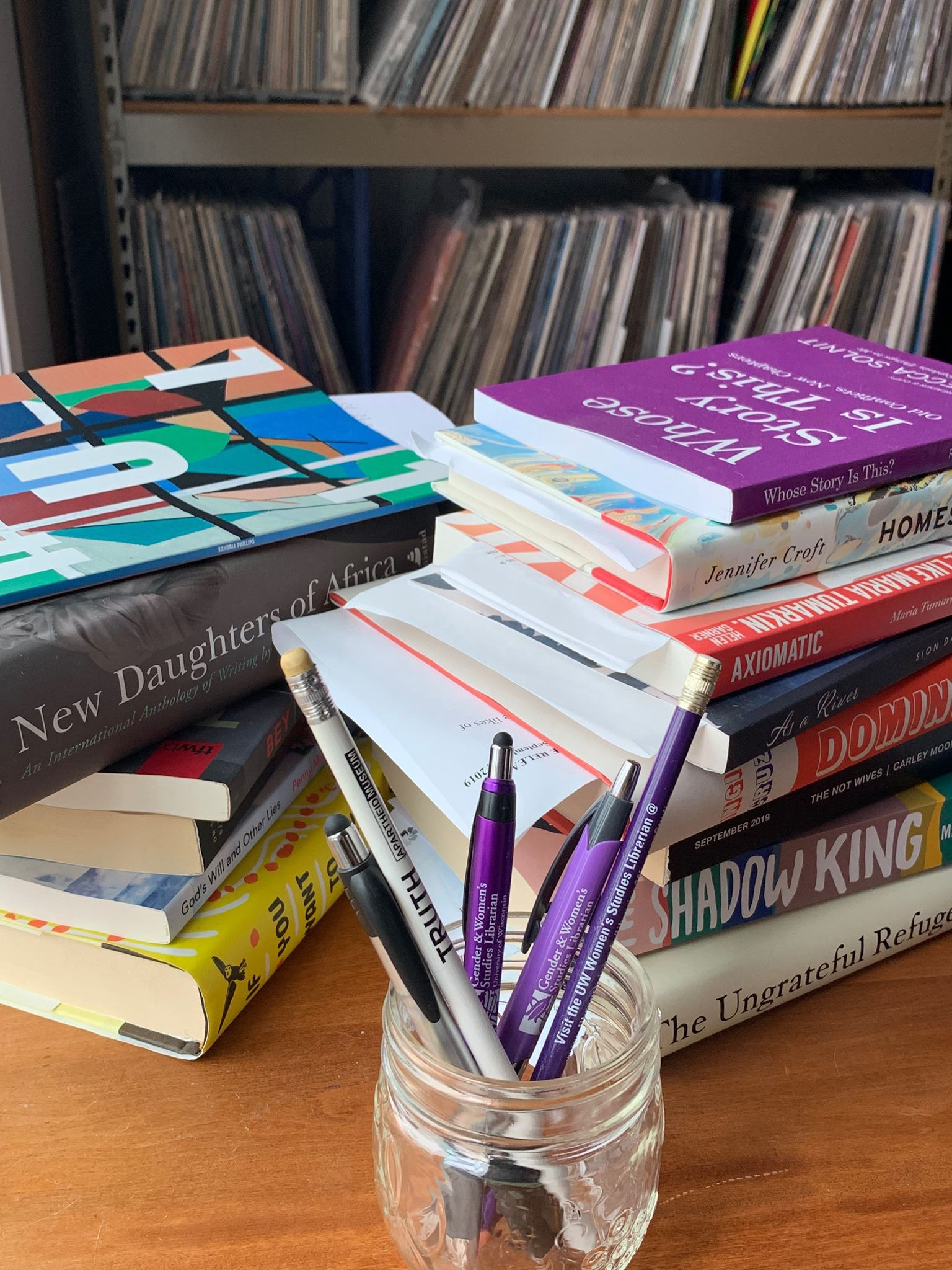 Photo by Karla Strand of two piles of books and a glass jar with purple and white pens and pencils in it.